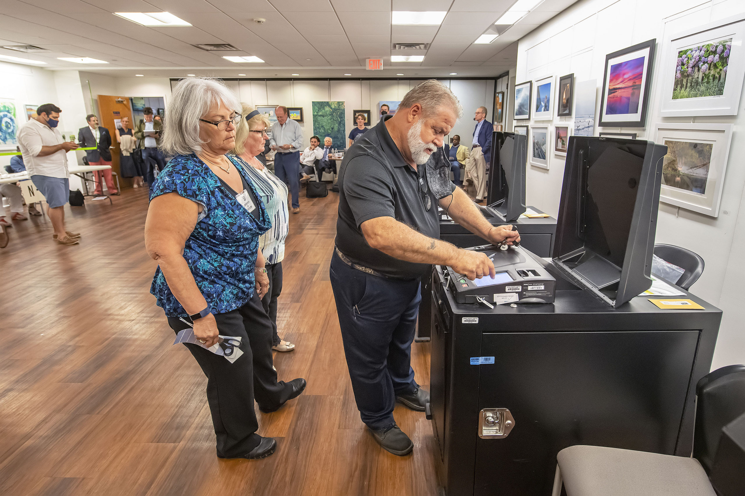 Election Inspectors look on as an election official retrieves the vote count from a voting machine during the 2021 Southampton Village Mayoral election at the Southampton Cultural Center on Friday night. MICHAEL HELLER
