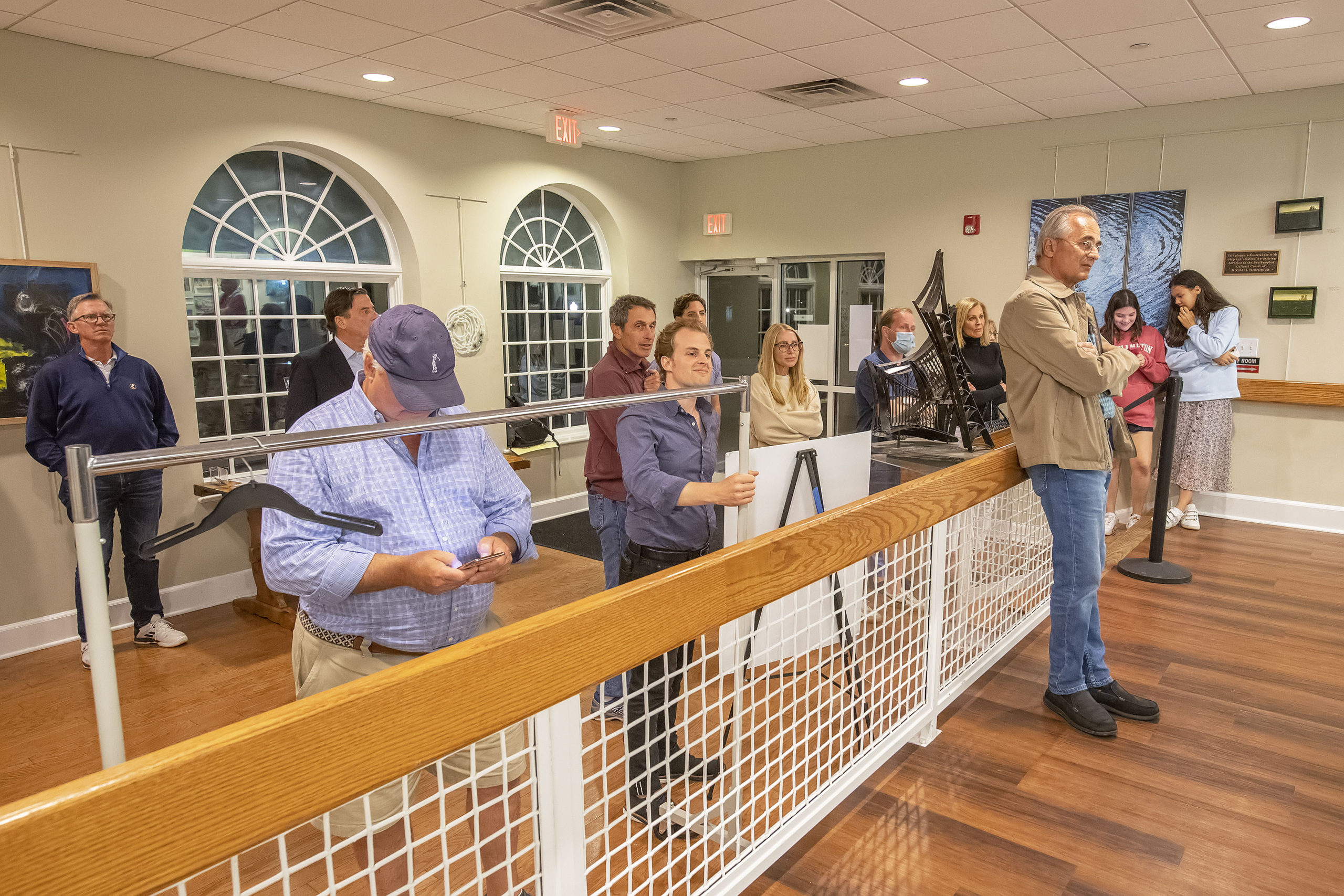 A gallery of interested persons watches from outside the main room as the vote count from each of the voting machines is tabulated during the 2021 Southampton Village Mayoral election at the Southampton Cultural Center on Friday night. MICHAEL HELLER