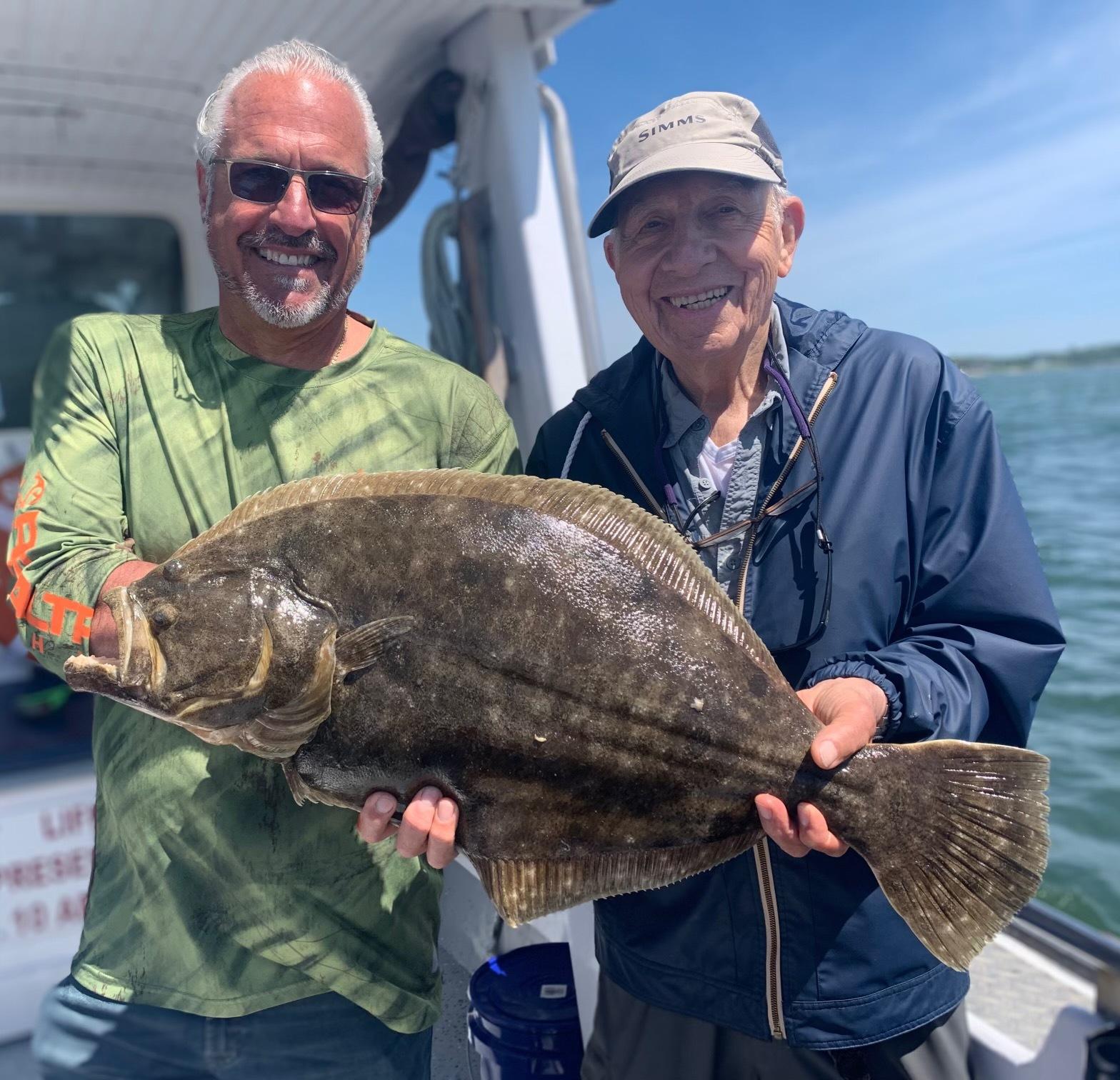 Capt. John Capuano helps Stan Kestenbaum show of the 10-pound 8-ounce fluke he caught aboard the Shinnecock Star last month.