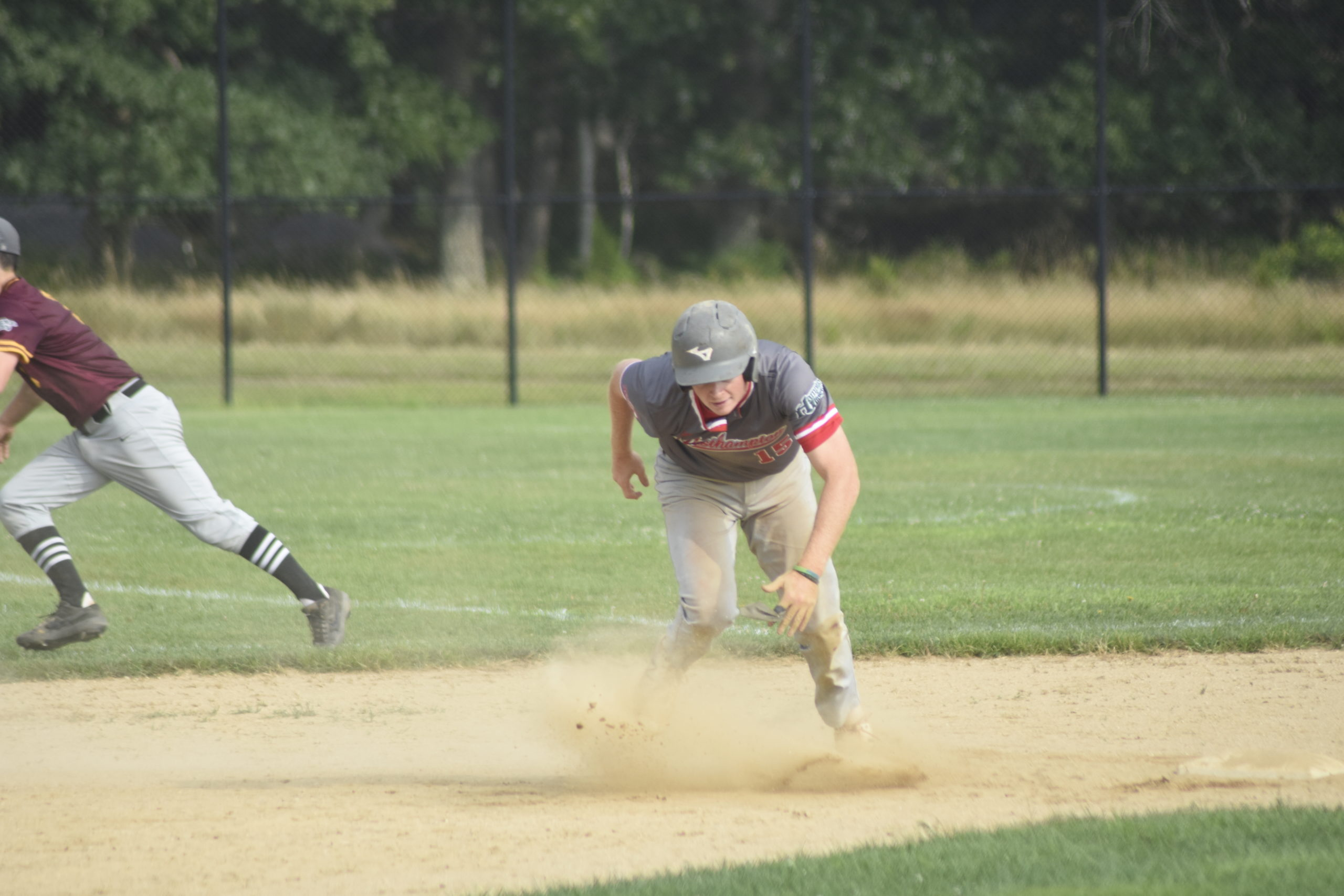 Matt Alifano (Adelphi/Center Moriches) races toward third base after an errant throw goes into the outfield as he stole second base.