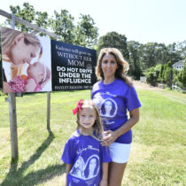 Susan Tocci with Kadence Podlas in front of the billboard.  DANA SHAW