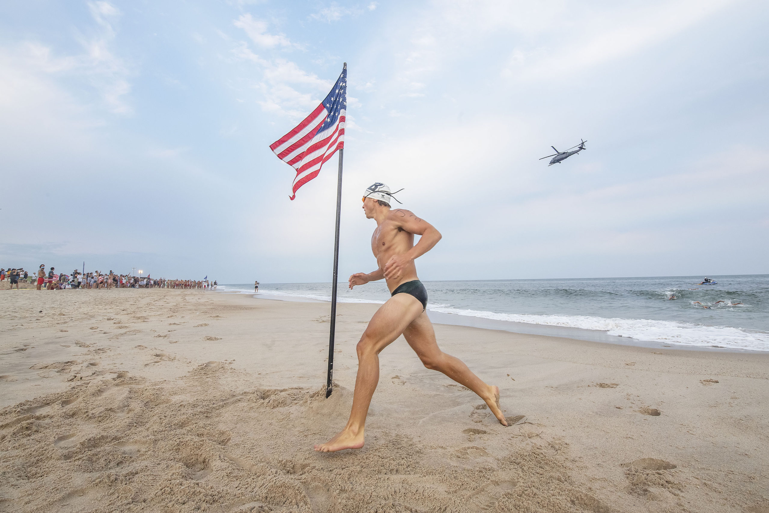 As a military helicopter passes by overhead, a Jones Beach competitor turns the corner at the American flag during the men's run-swim-run competition at East Hampton's Main Beach Lifeguard Competition on July 22.