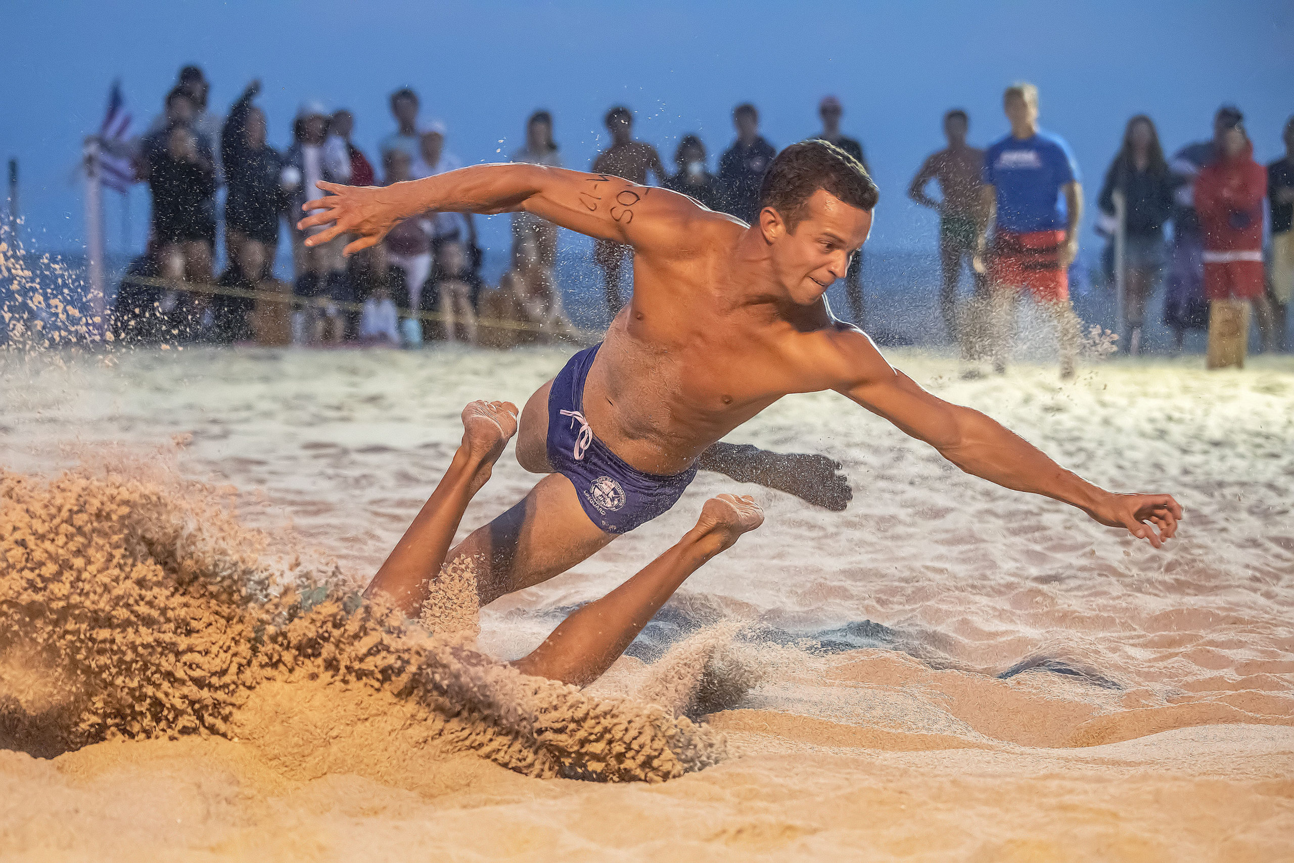 Southampton Town lifeguard Casey Crowley reaches for a flag at the finish line during the men's beach flags competition.