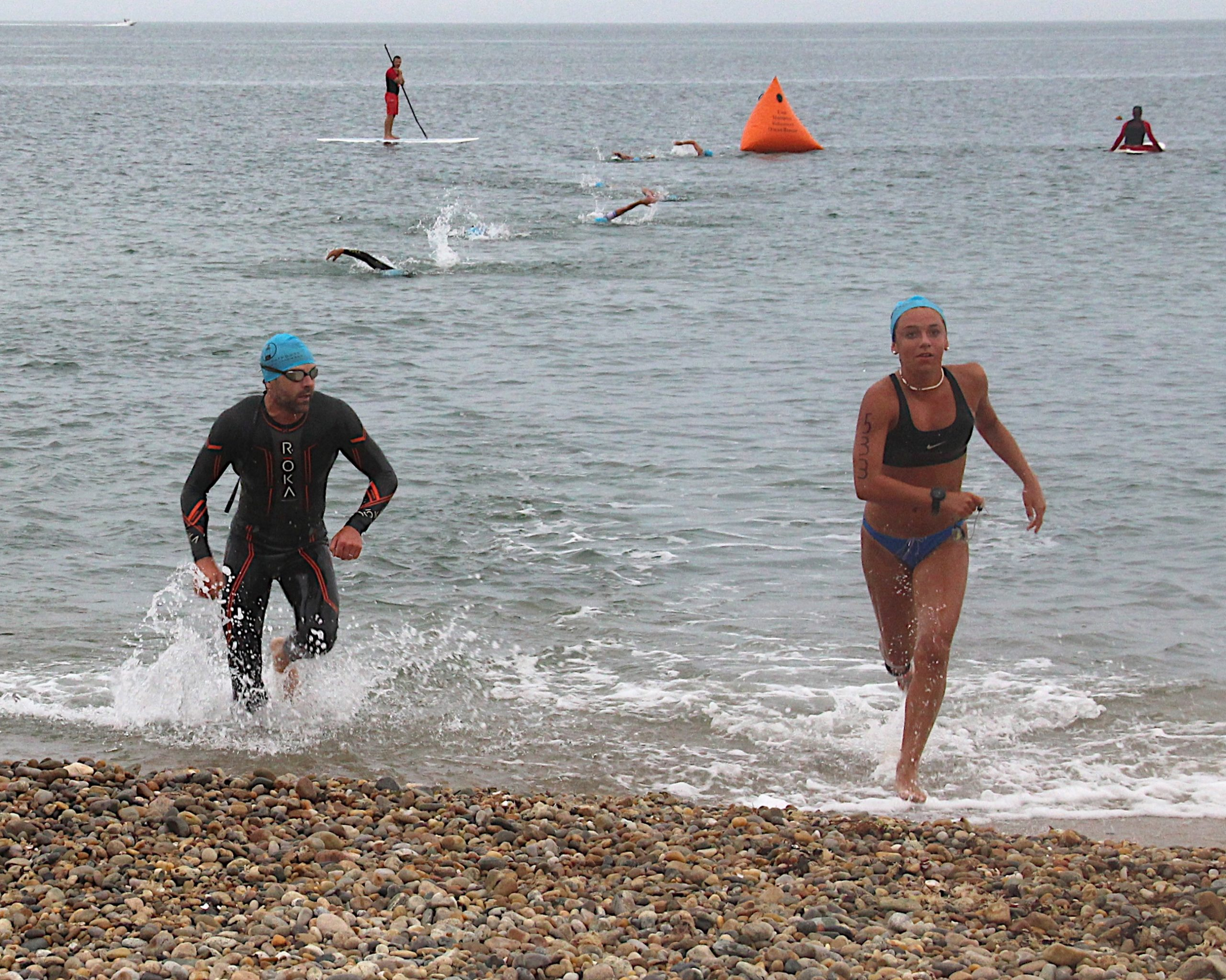 After completing the swimming portion of the triathlon, athletes get out of the water and head toward their bikes to start the cycling portion.
