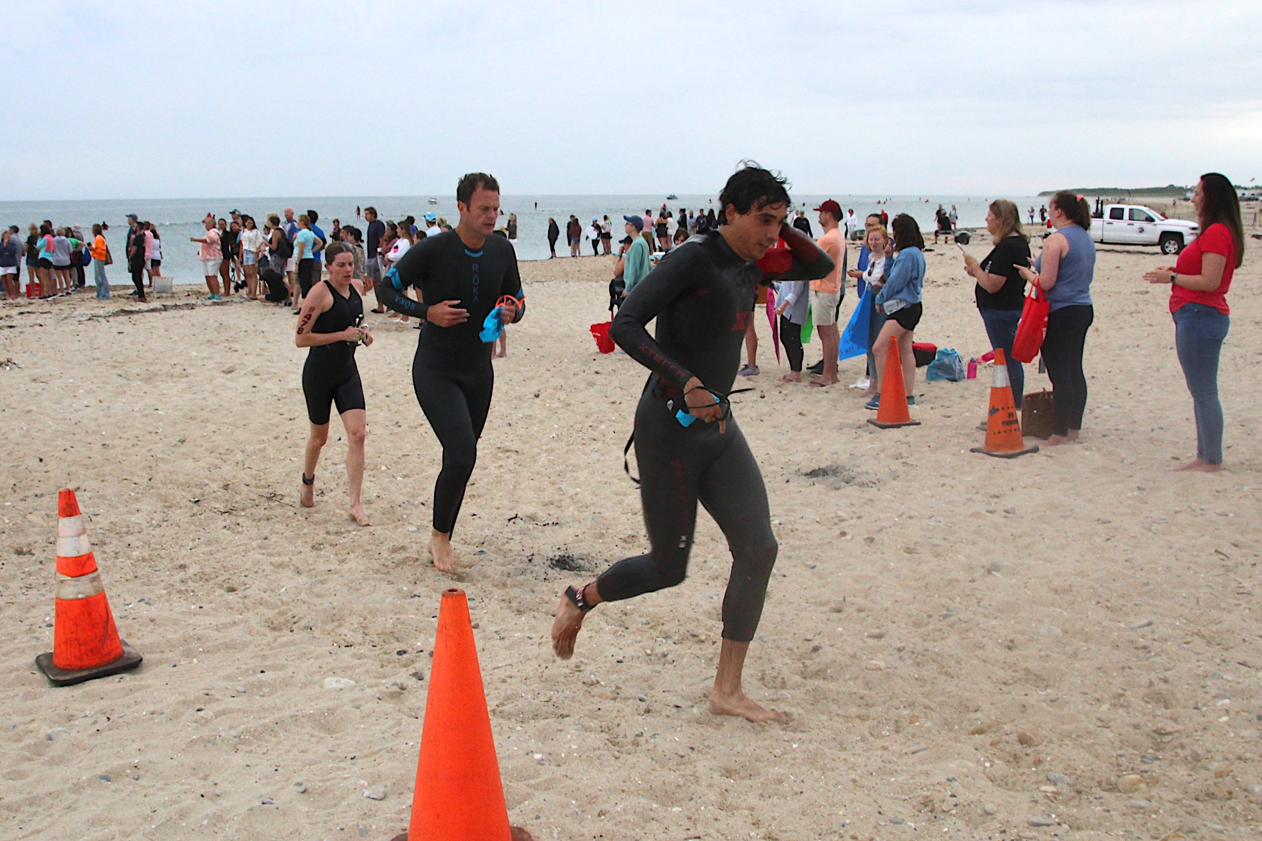 Triathletes gets out of the water and head toward their bikes to start the cycling portion of the race.