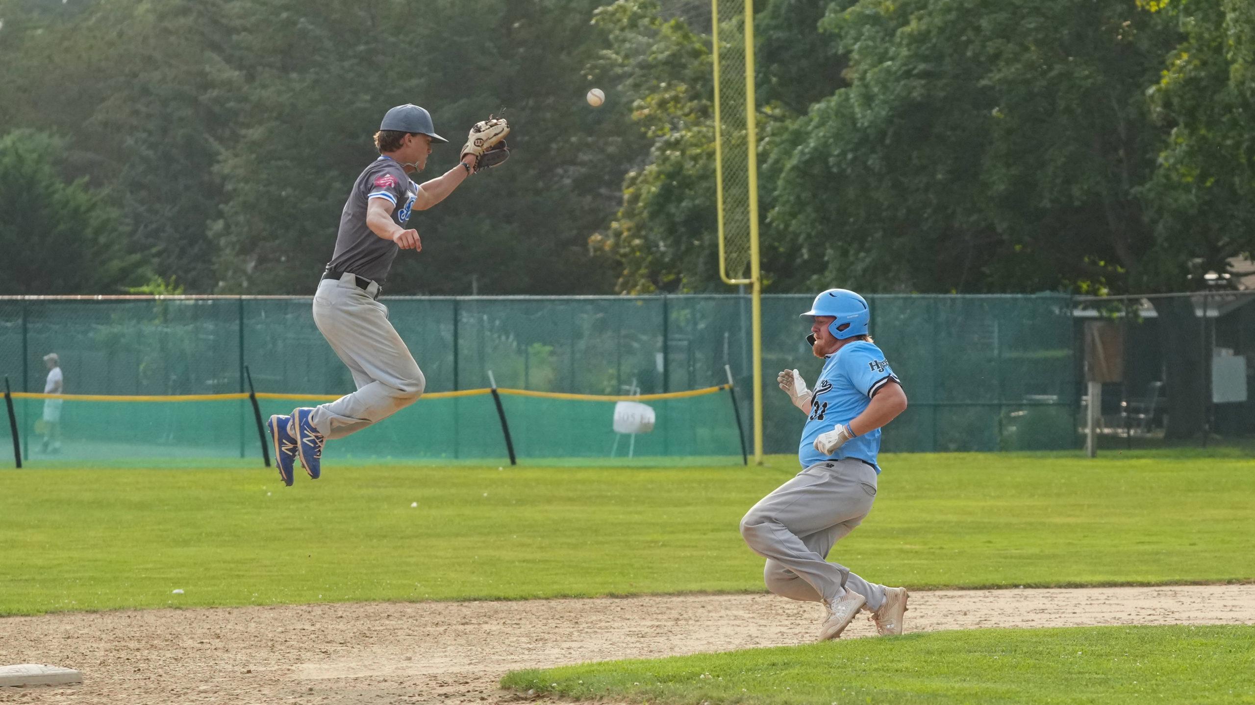 Southampton shortstop Thomas Eitniear (Toledo) leaps out of the way of sliding Sag Harbor Whaler Ryan Mullahey (LIU).