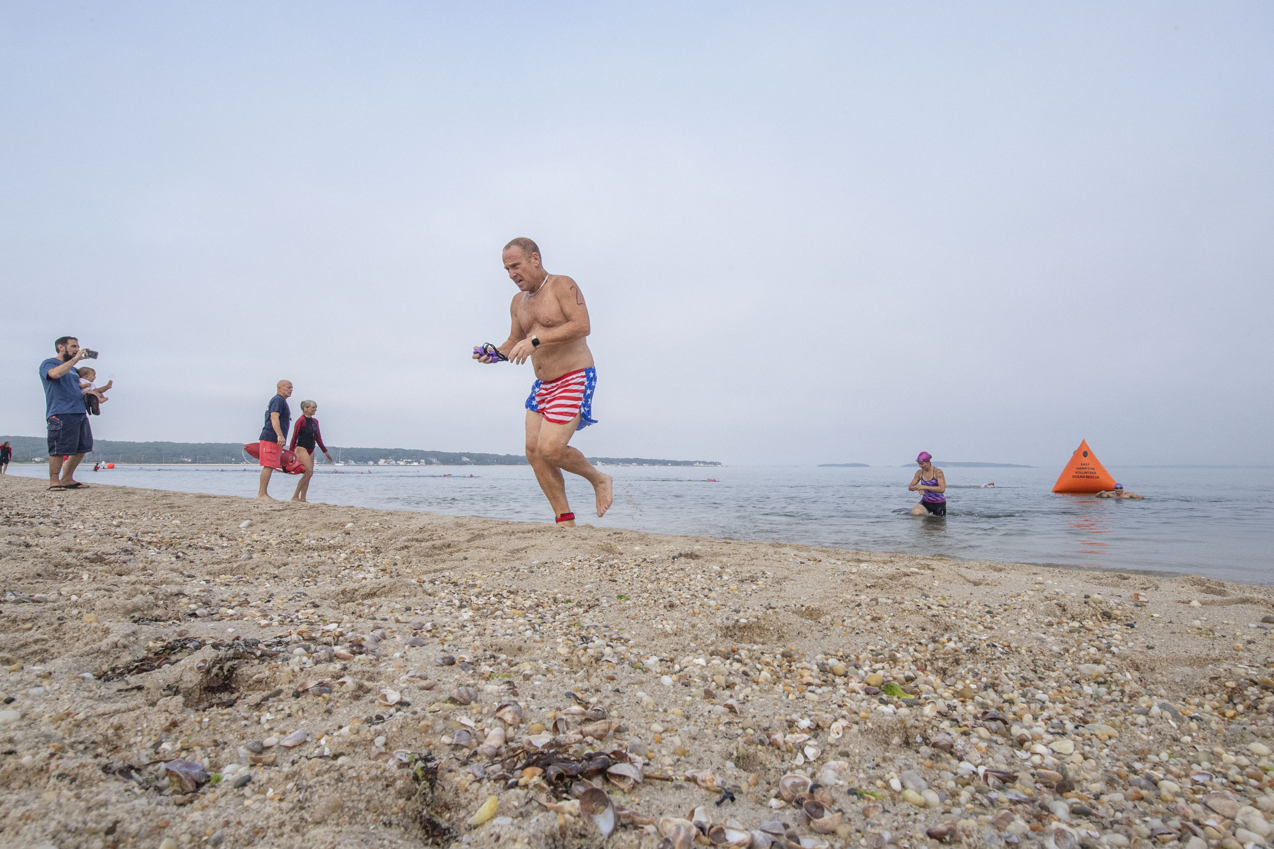Competitors exit the water during the first leg of the Hamptons Young at Heart Triathlon.