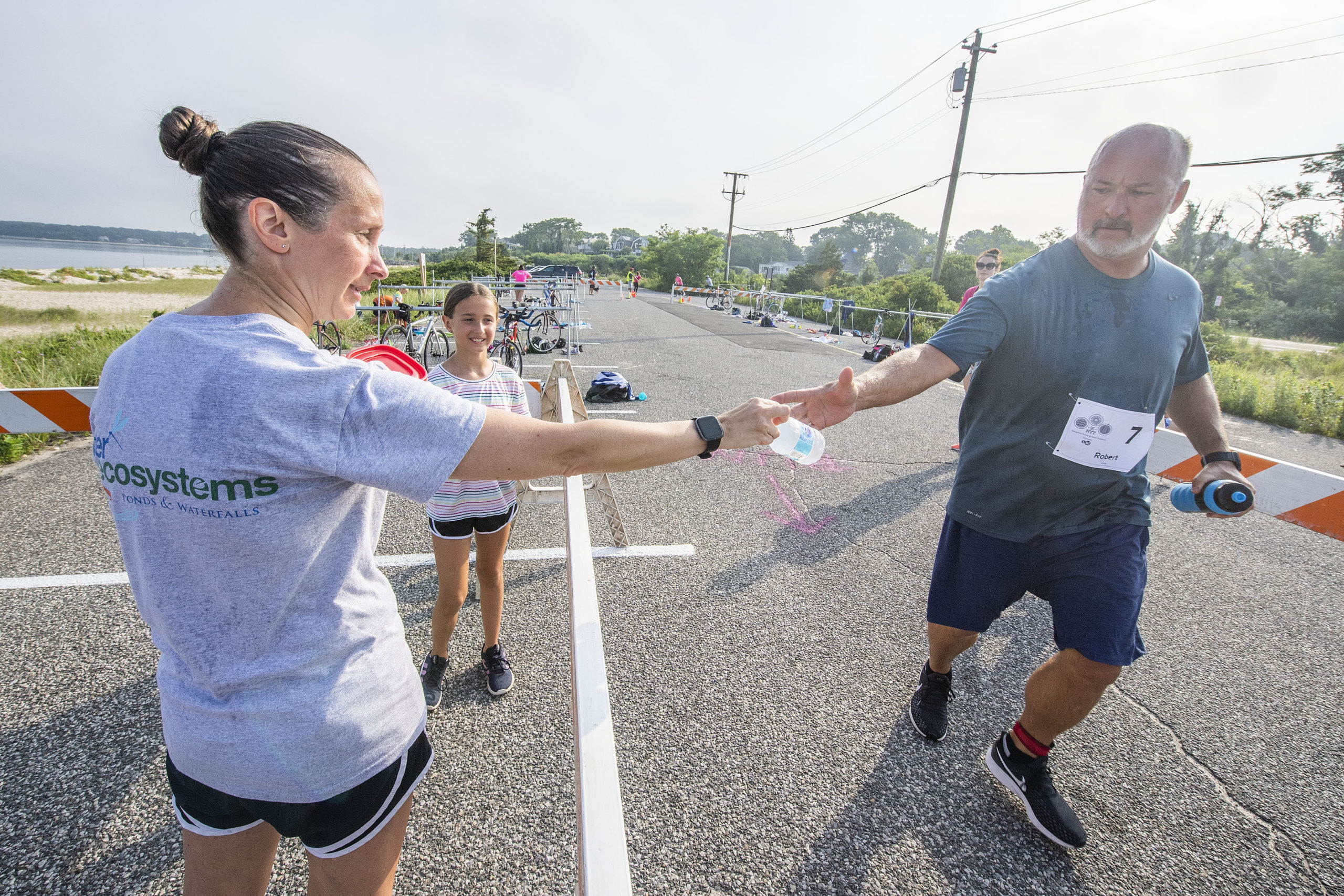 Sarah and Emily Drohan hand out bottles of water to the contestants during the Hamptons Young at Heart Triathlon.