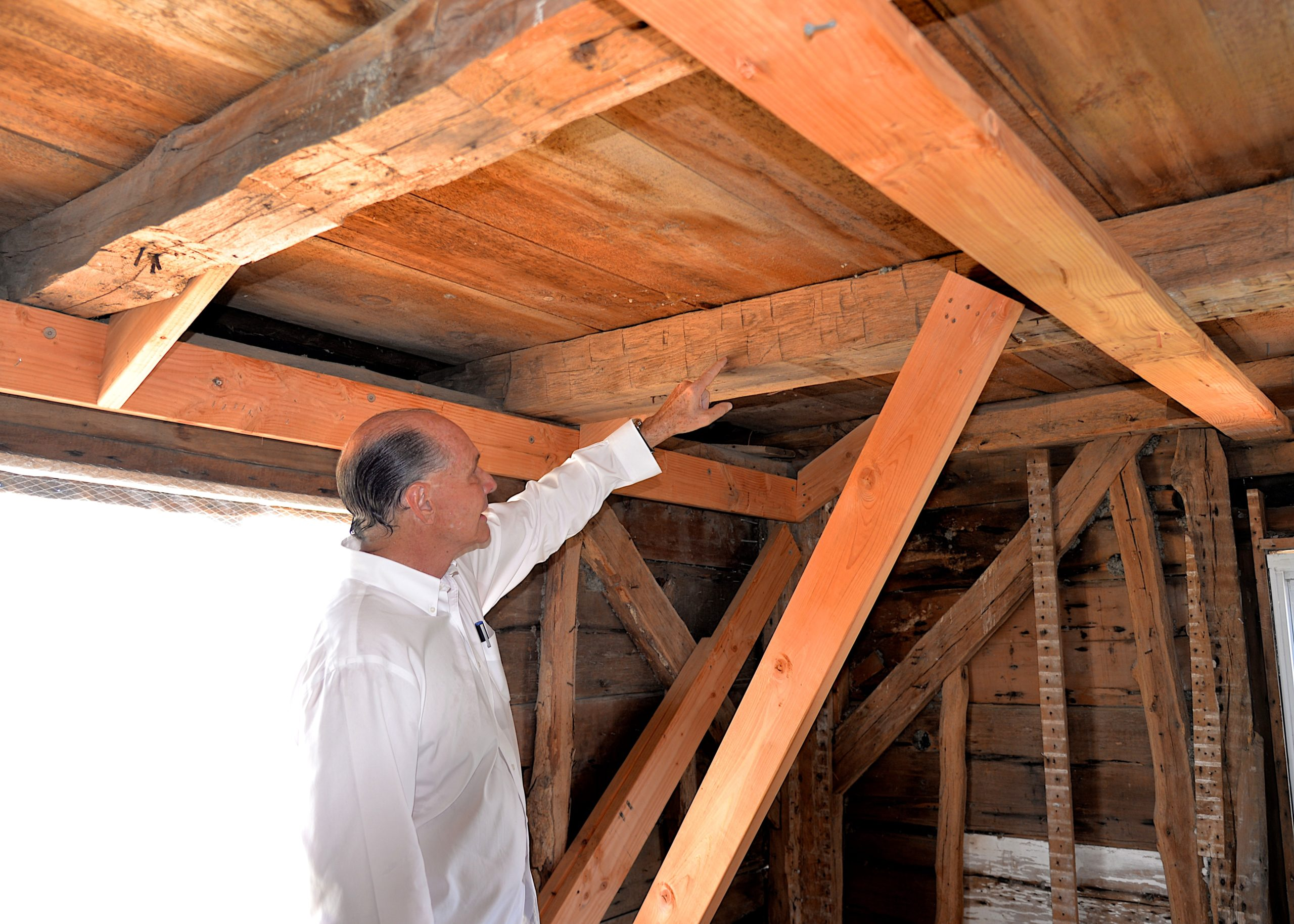 Jeffrey Colle shows off the hand-hewn beams in the historic home.KYRIL BROMLEY