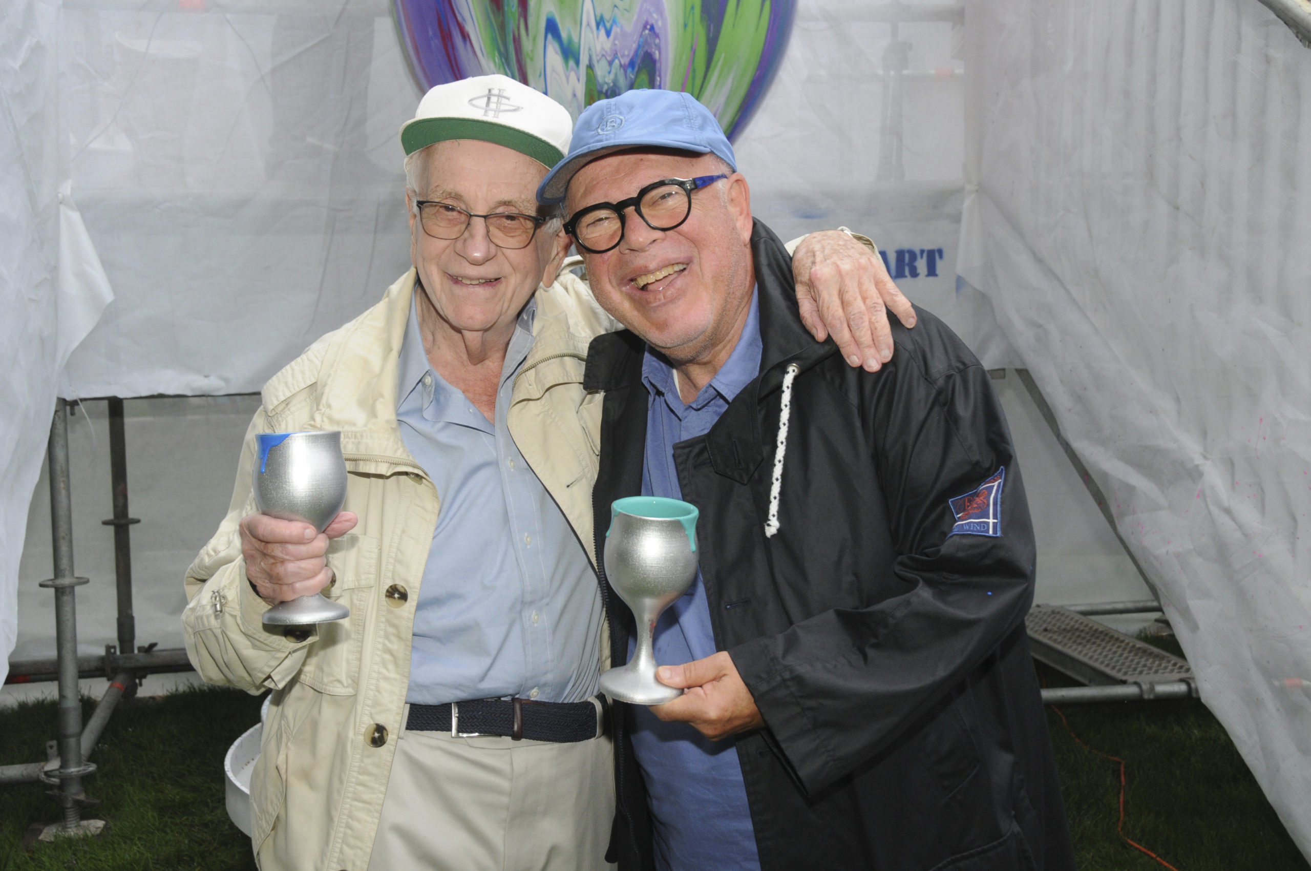 """Bernard Goldberg and Norman Stark, two of the founders of the Chabad of the Hamptons, at the 11th Annual Benefit, called """"Overflowing Blessings"""" on August 8. Guests had a chance to brush up on their art skills, as they took turns pouring cups of paint over the eight foot tall Kiddush Cup by Yitzchock Moully, the Pop Art Rabbi.     RICHARD LEWIN"""