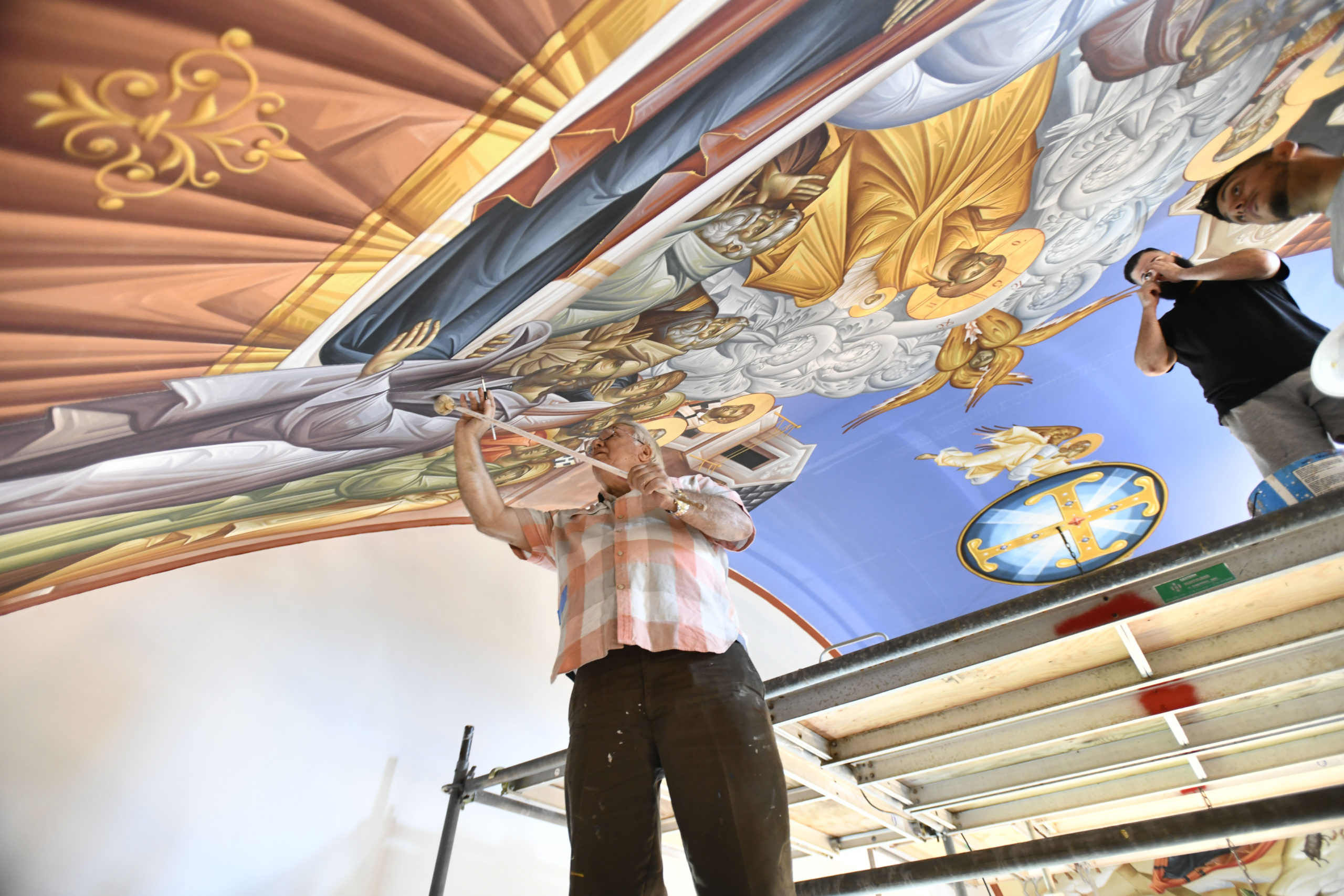 Iconographer George Filippakis works on the ceiling of the Dormition of the Virgin Mary Greek Orthodox Church on Monday. The church will be his last work.  DANA SHAW