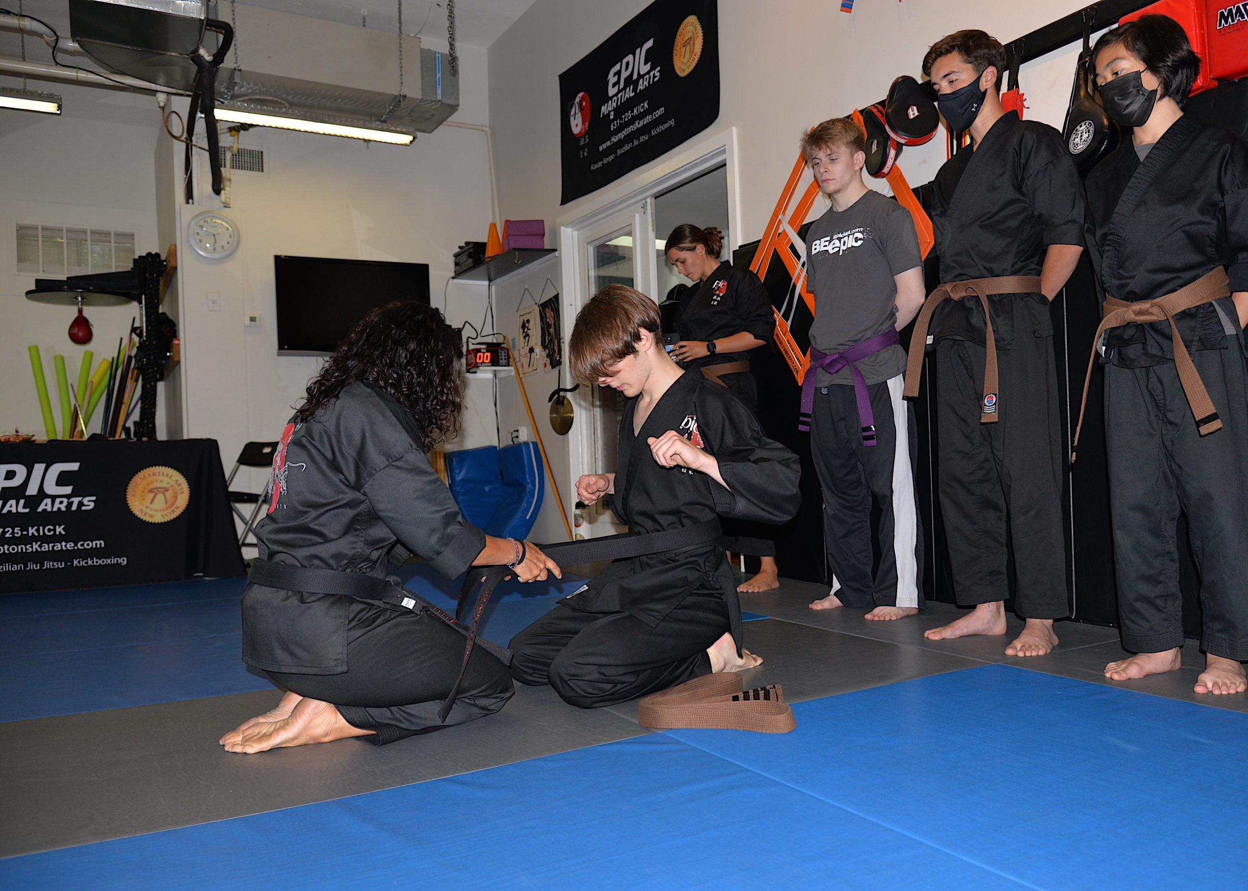 Sensei Michelle Del Giorno presents Thomas Schiavoni his black belt.