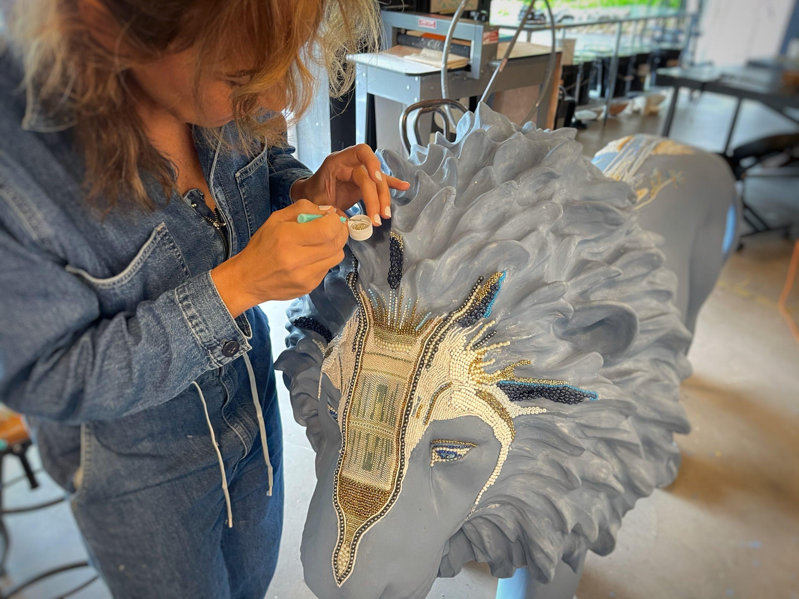Elizabeth Jordan works on her lion sculpture,