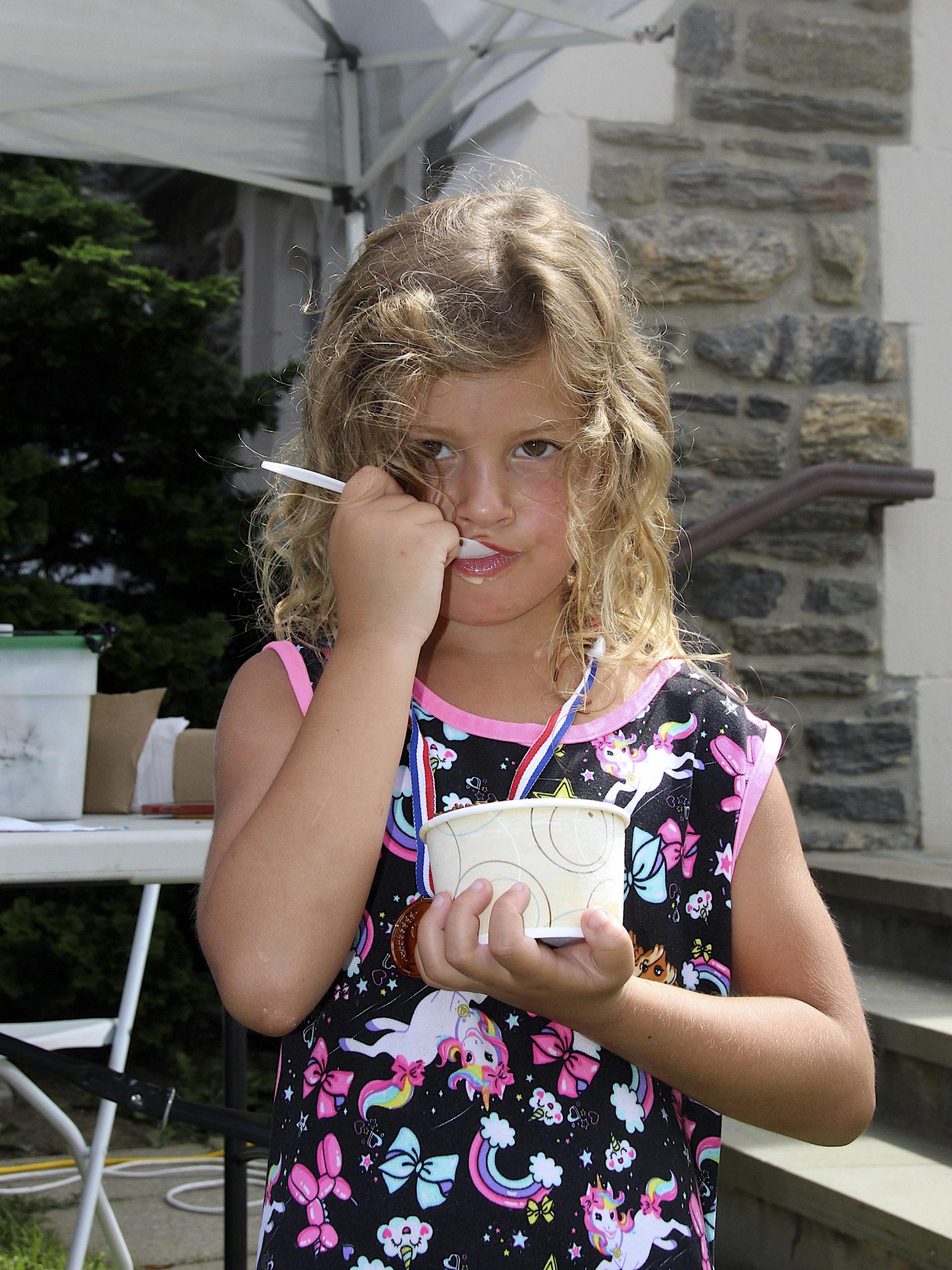 Paisley Bennett enjoys some ice cream at the St. Luke's Episcopal Church Fair on Saturday.  KYRIL BROMLEY