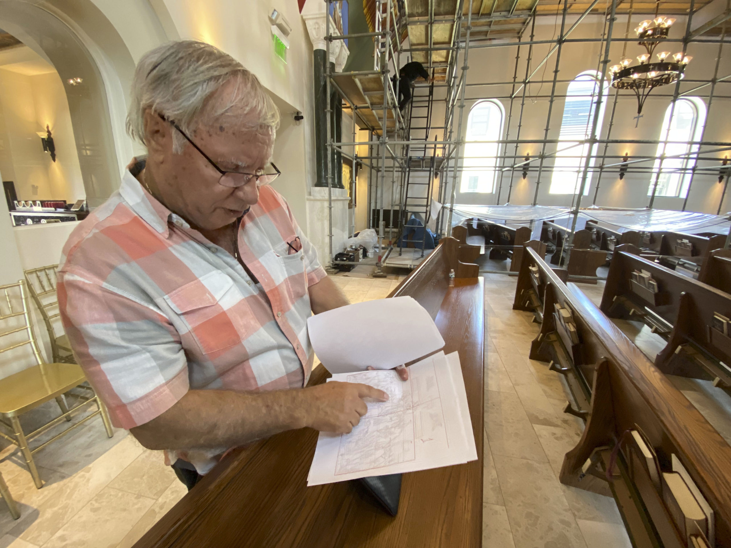 Iconographer George Filippakis  with sketches of the remaining works on the ceiling of the Dormition of the Virgin Mary Greek Orthodox Church. The church will be his last work.  DANA SHAW