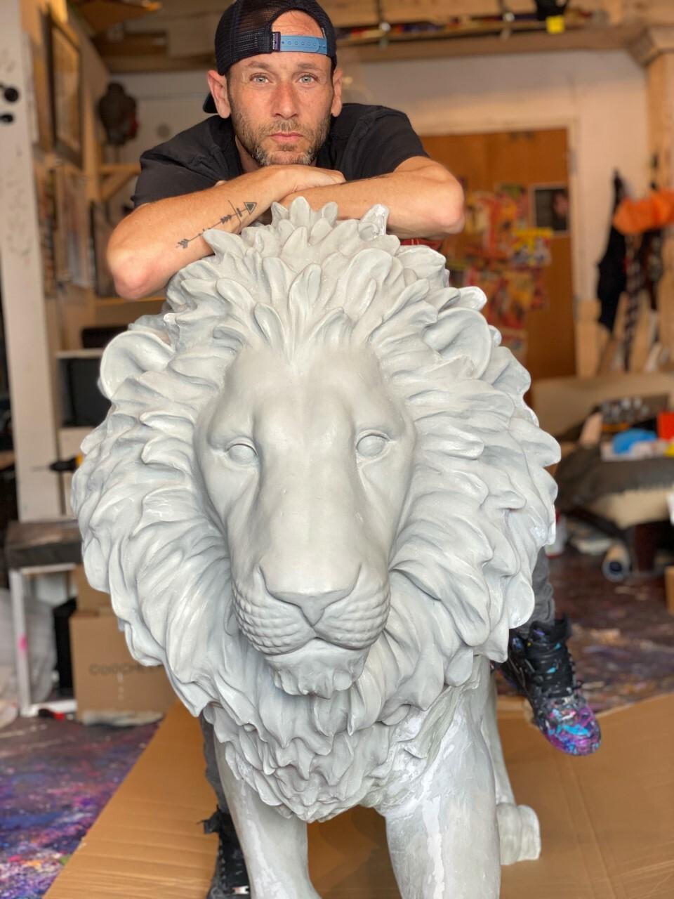 Jeremy Penn with his lion sculpture.