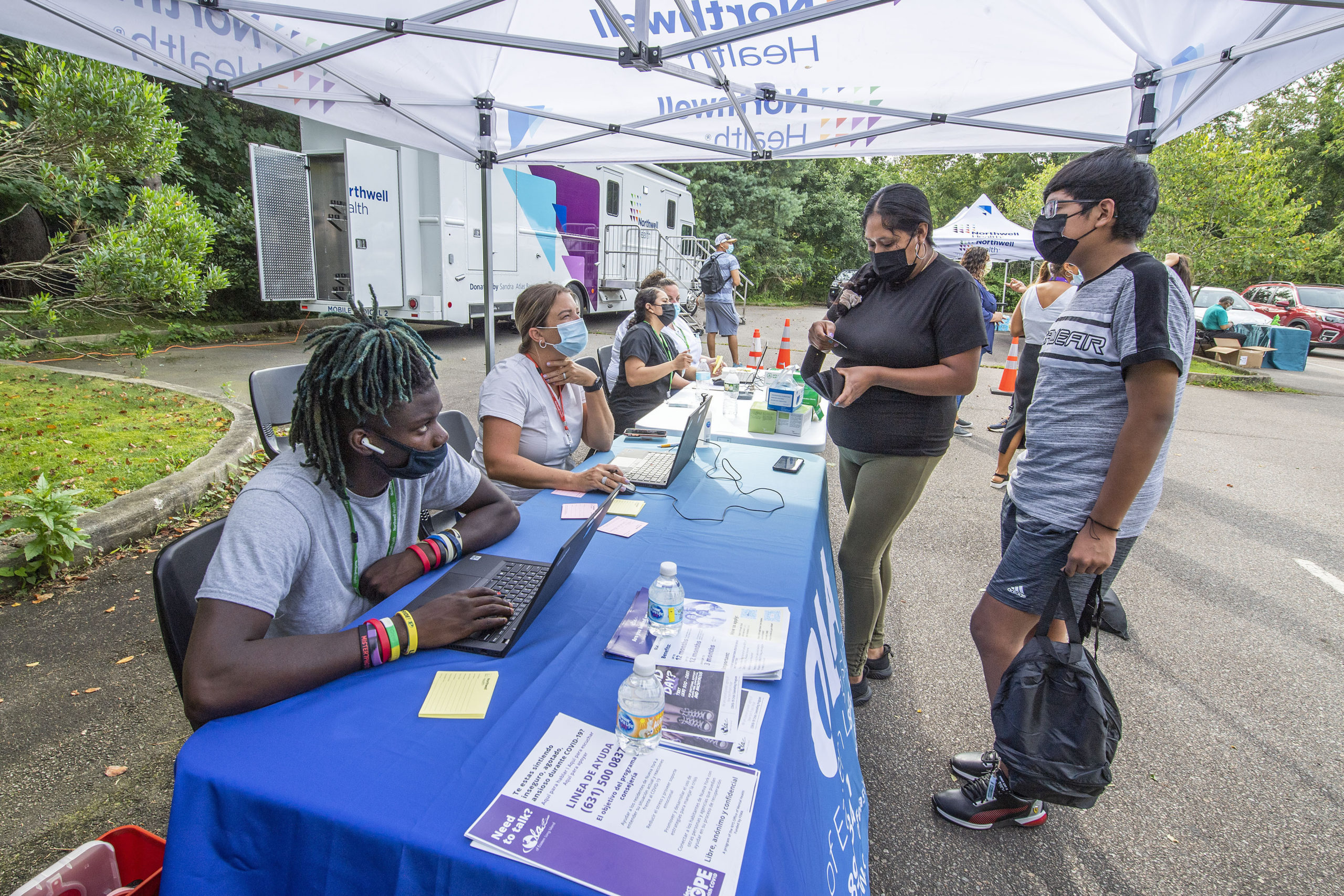 Applicants check in at a registration desk at a pop-up COVID-19 vaccination site that was organized and hosted by the OLA of Eastern Long Island in conjunction with Northwell Health in the parking lot of the Children's Museum of the East End in Bridgehampton on  August 19.  MICHAEL HELLER