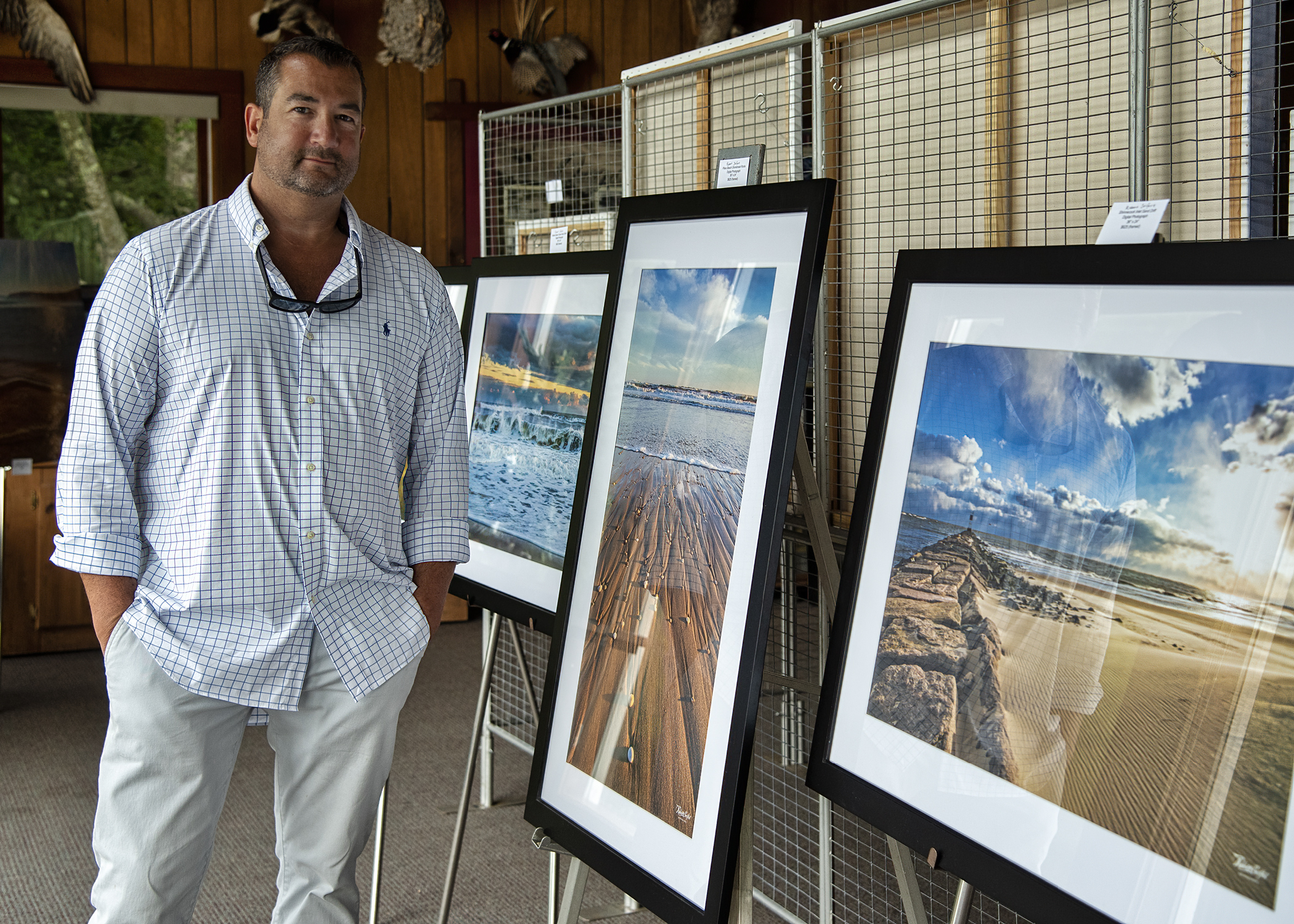"""Rob Seifert, by his photography, at an artists showcase, """"Visions of Nature Art Exhibition,"""" curated by Elizabeth Hartman of HartmanonHudson.com, at the Quogue Wildlife Refuge on Saturday. A portion of the evening's sales benefited the refuge."""
