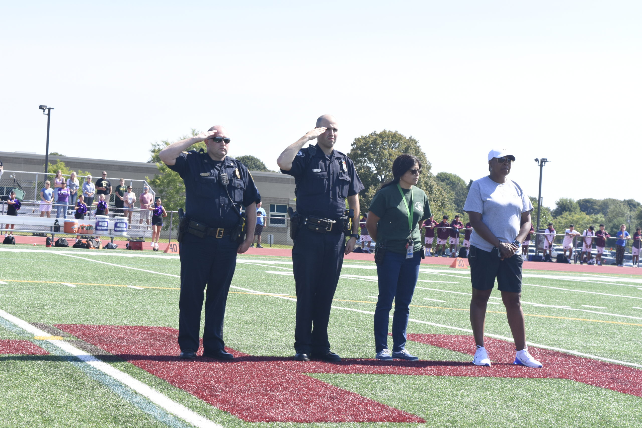 East Hampton Village Police Officer Matthew Morgan, left, East Hampton Town Police Officer Joseph Izzo and East Hampton Village Ambulance members Marcia Dias and Samone Johnson salute the American flag during the singing of the Star Spangled Banner prior to the East Hampton football game this past Saturday, September 11.