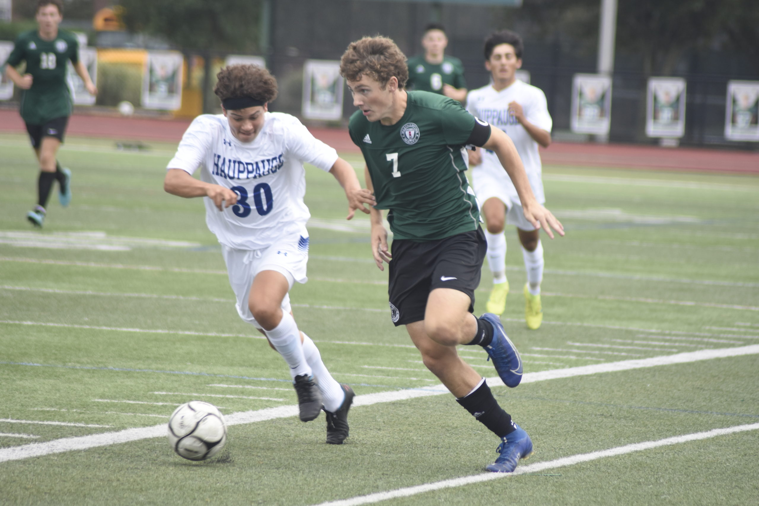 Westhampton Beach senior co-captain Andre Insalaco and a Happauge player battle for ball possession at midfield.