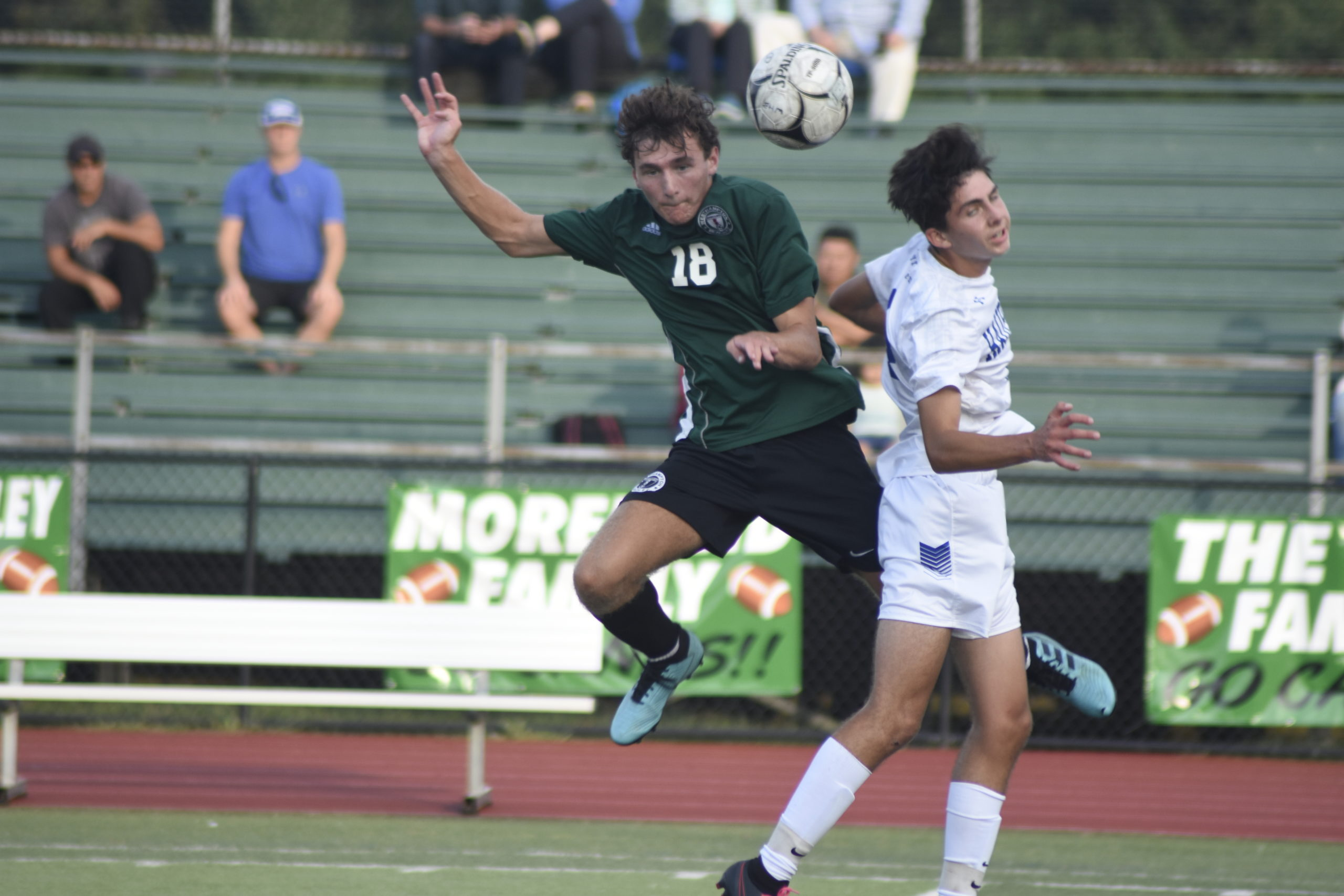 Westhampton Beach senior Michael Griffin and a Hauppauge player collide mid-air going up for a free ball.