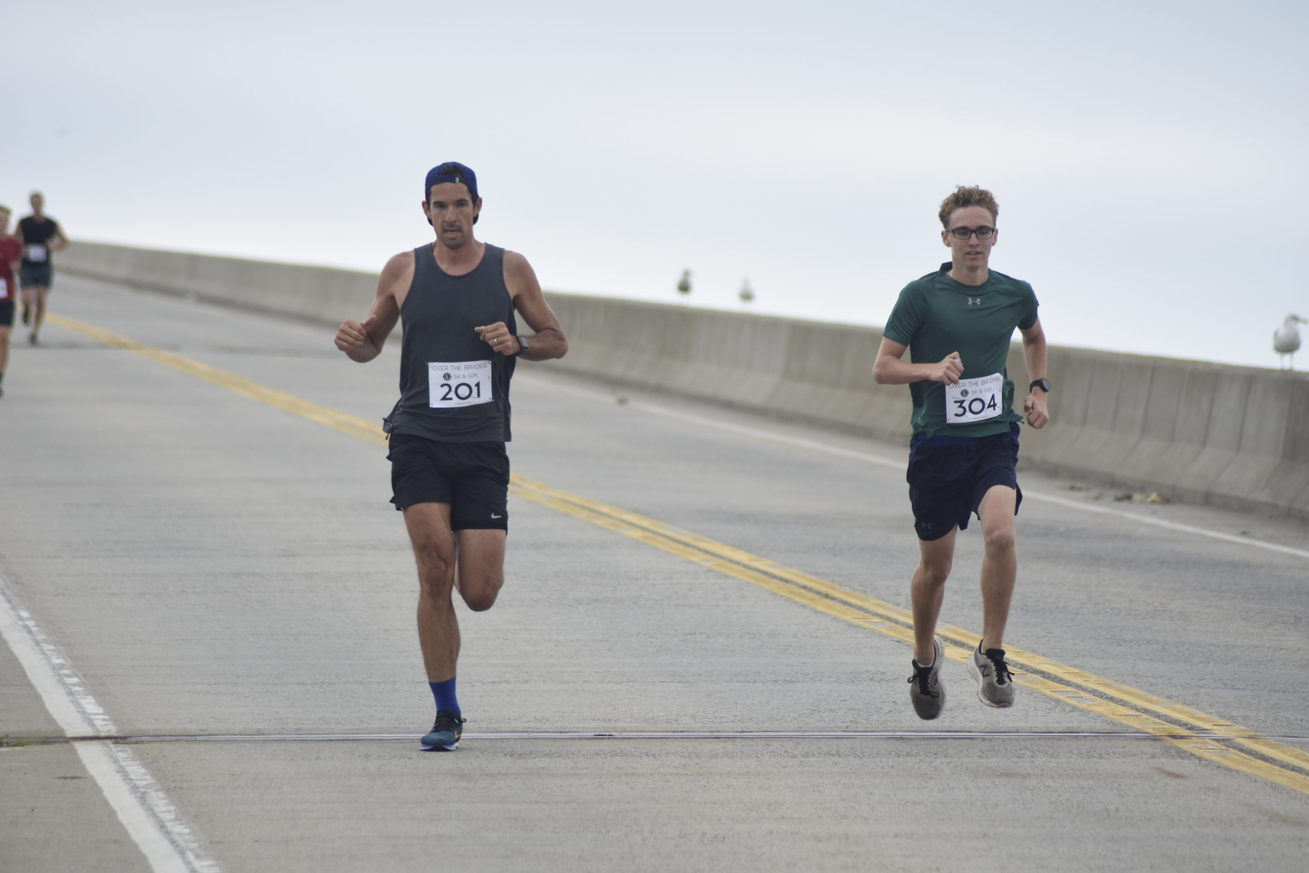 Jack Stevens, left, and Luca Villano lead the initial pack of runners over Ponquogue Bridge on Saturday morning. Stevens and Villano finished first and second, respectively, in the 5K.