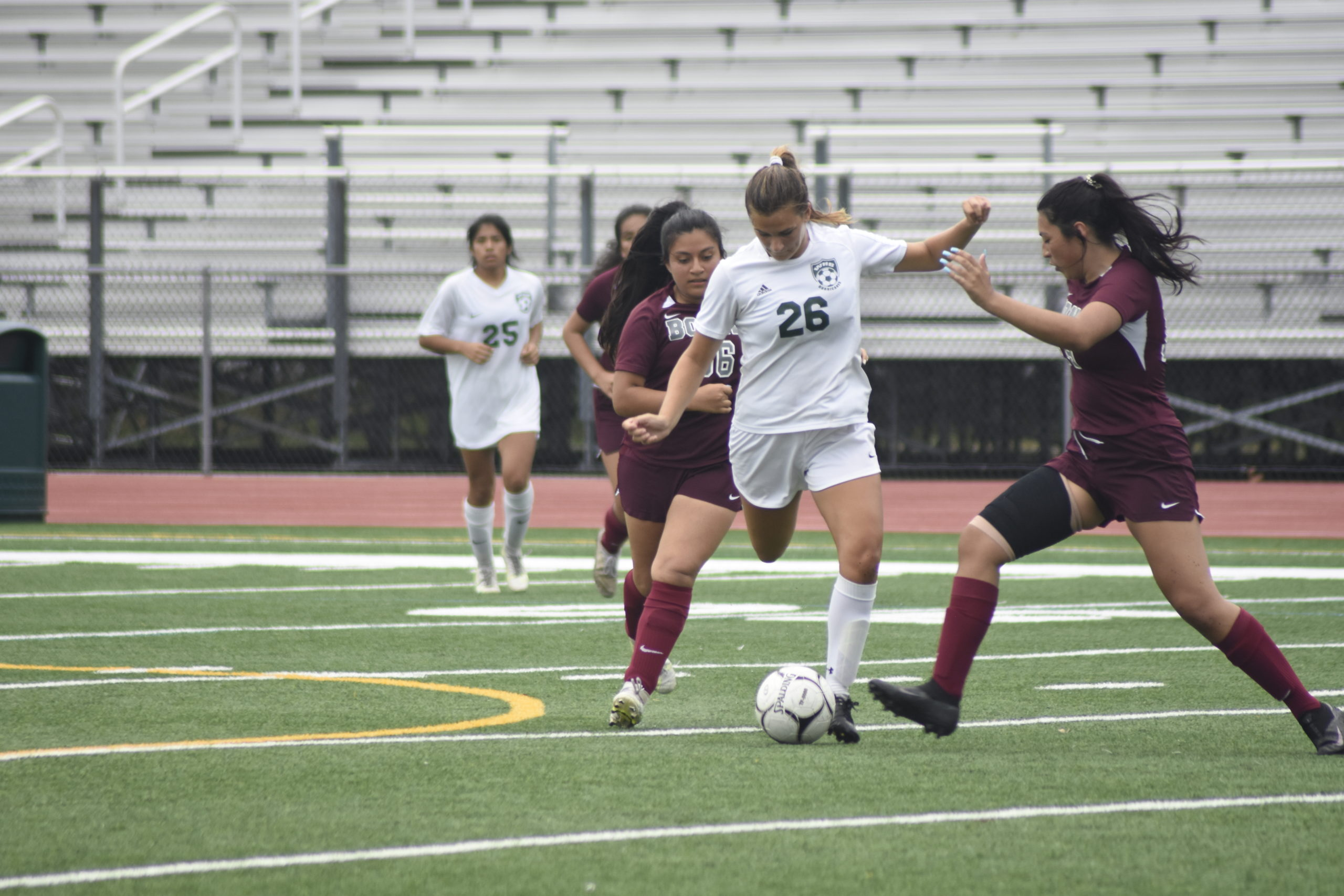 Sensing pressure from a pair of East Hampton players, Westhampton Beach junior Isabella Blanco clears the ball.