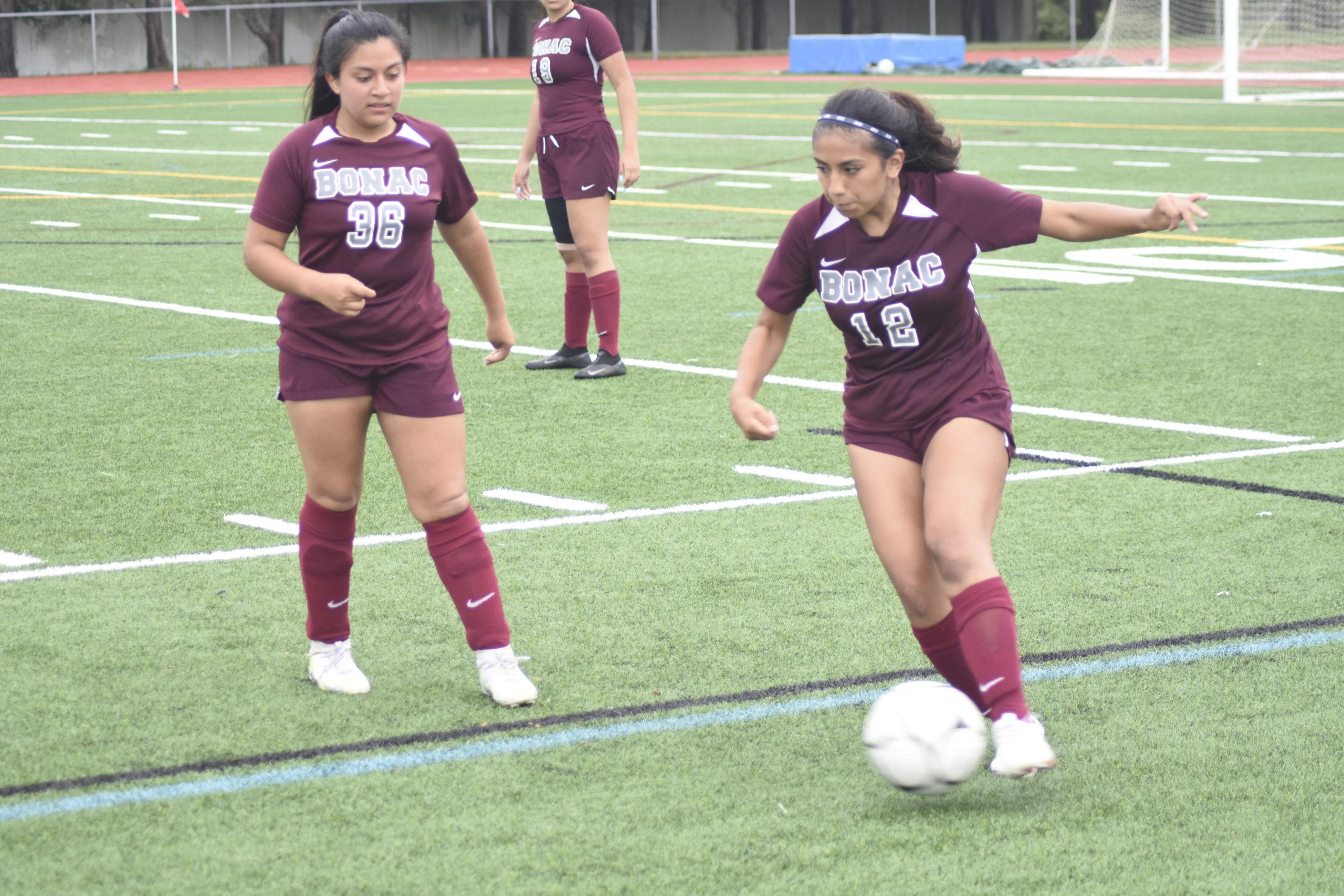 With junior Tiffany Pesantez looking on, junior Bonacker Nicole Velez plays the ball near the sideline.
