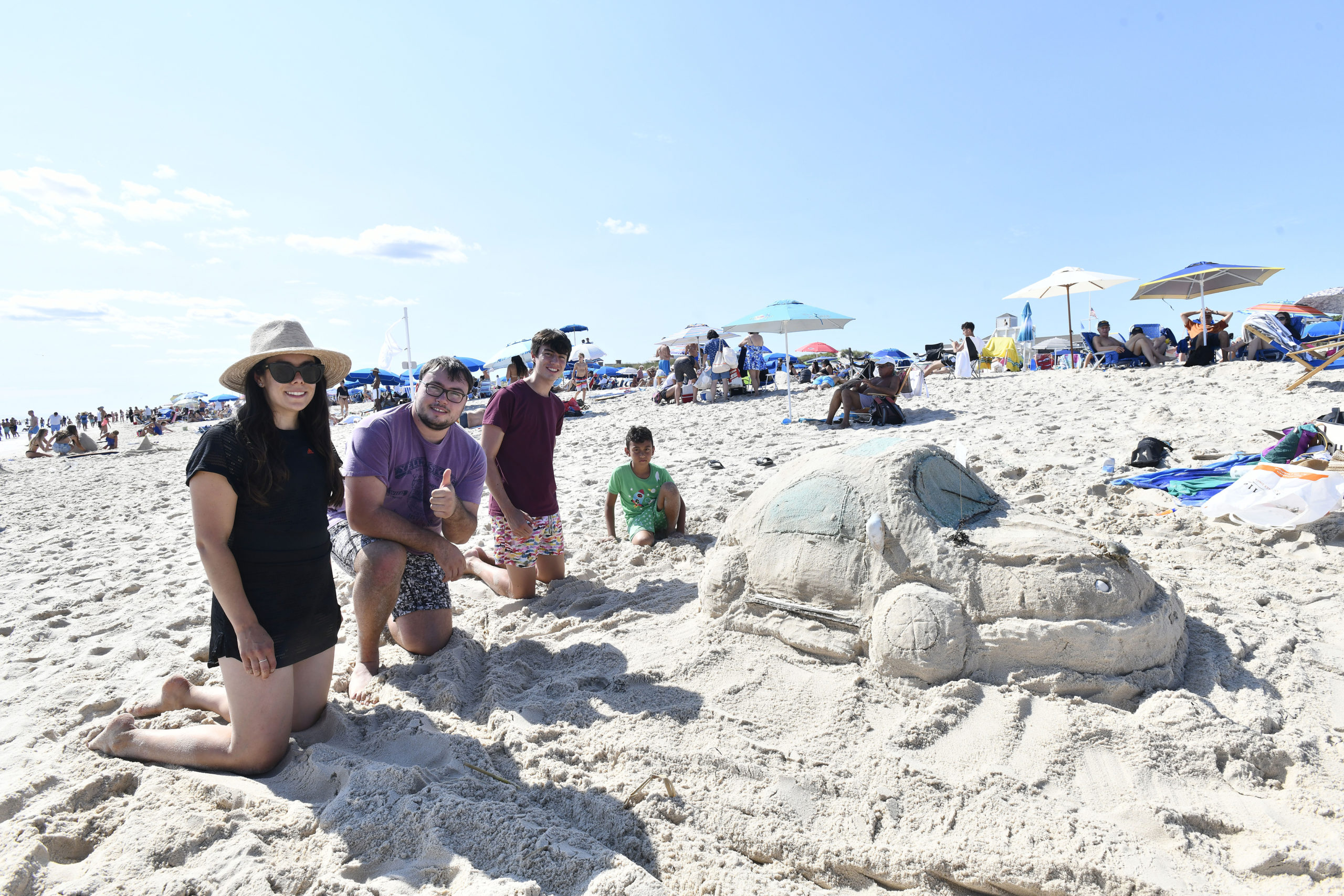 Gloria Dios, Ted and Nate Loquet and Sati Dios with their Volkswagen Bug at the Coopers Beach Annual Sandcastle Contest on Saturday afternoon.  DANA SHAW