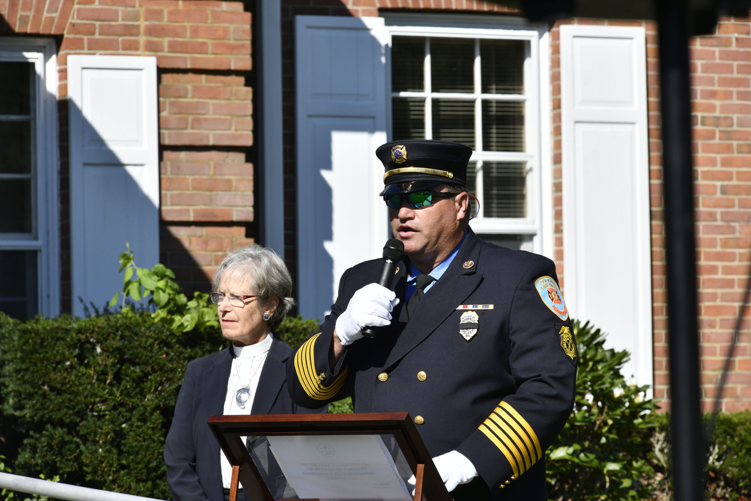 Quogue Fire Department Ex-Chief Chris Osborne welcomes the crowd the memorial rededication ceremony on Saturday.
