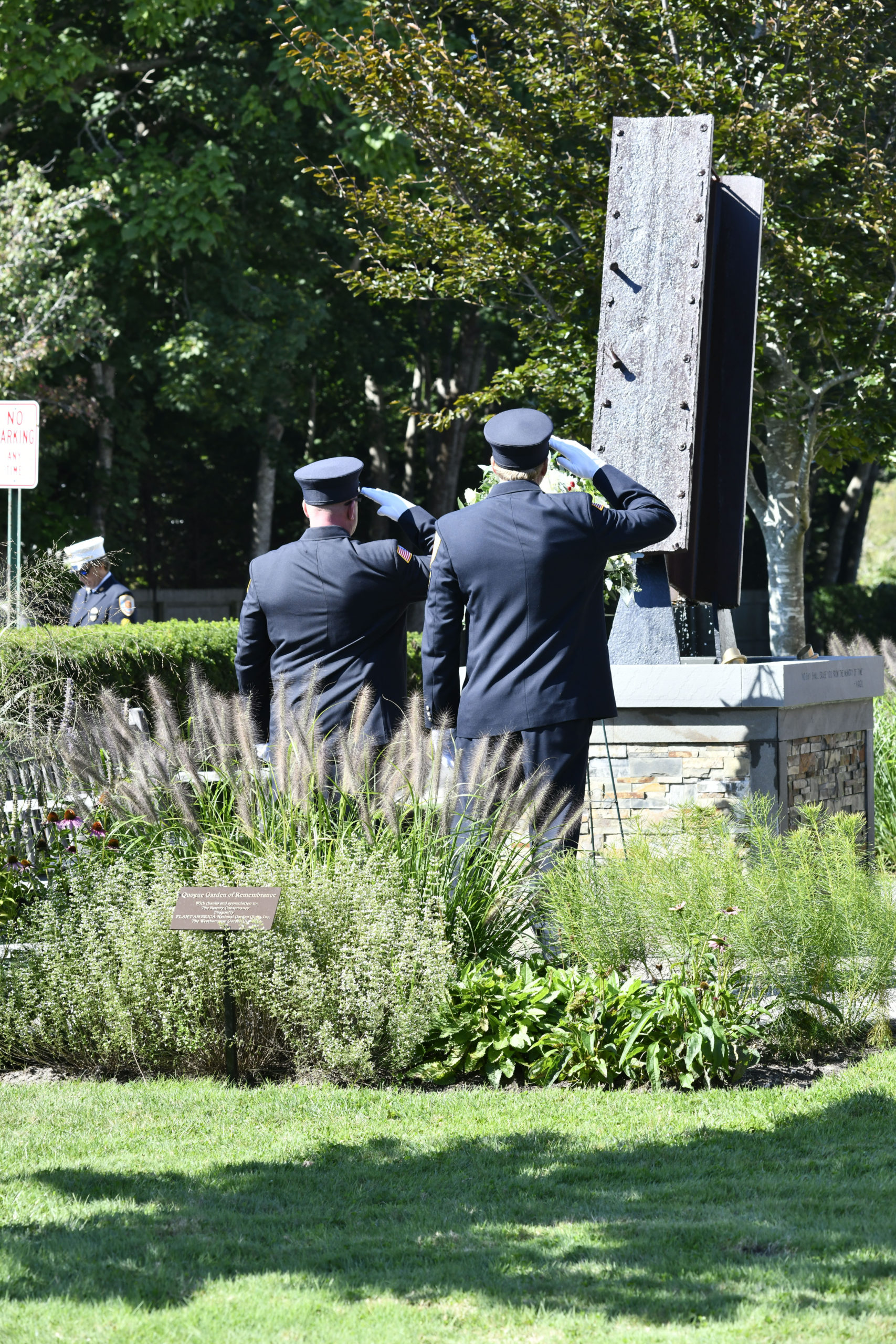 Quogue Firefighters salute the memorial on Saturday.