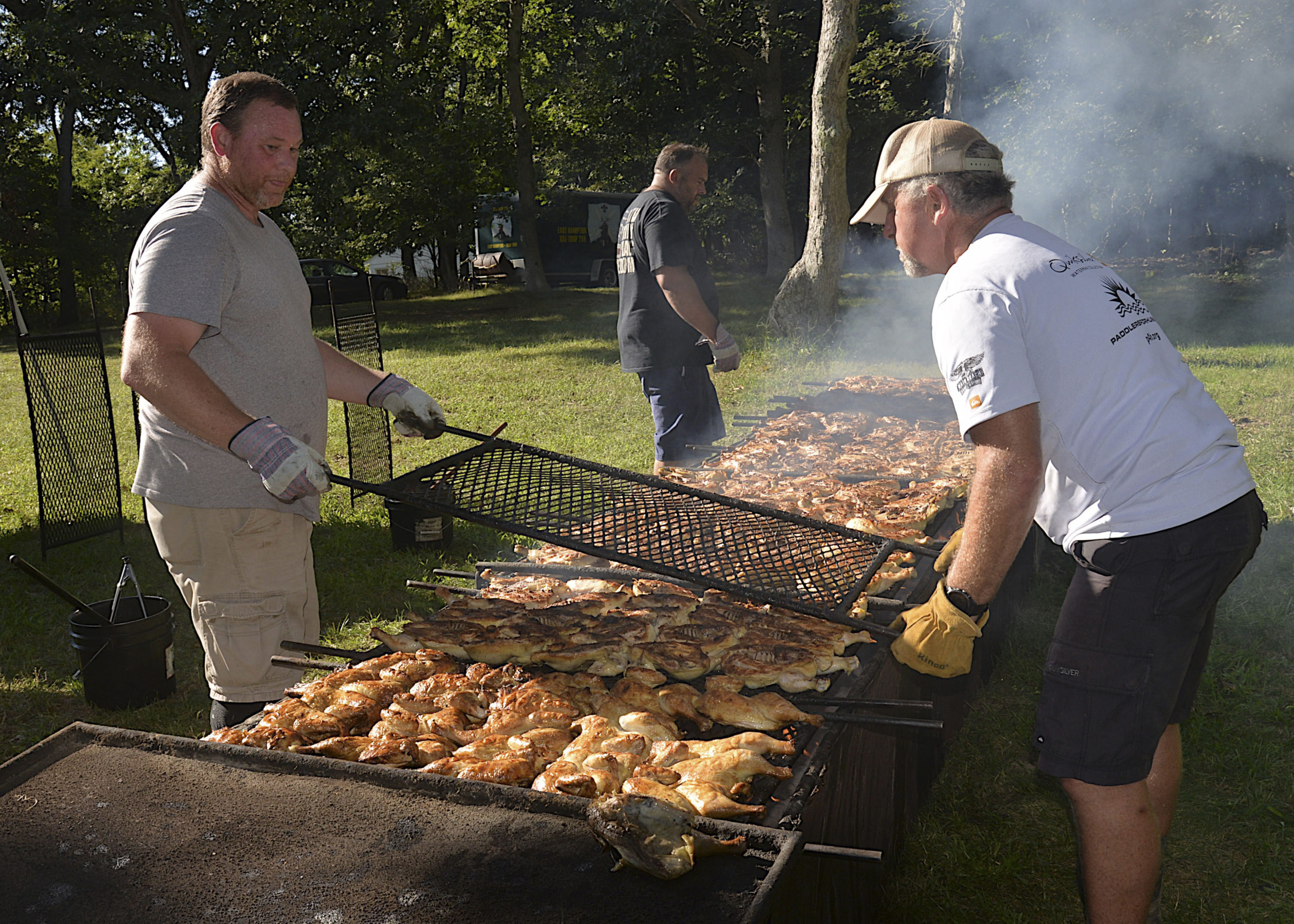 Steve Lynch Jr and Bob Pucci prepare the birds at the East Hampton Lions Club chicken barbeque at the Amagansett American Legion on Saturday.  KYRIL BROMLEY