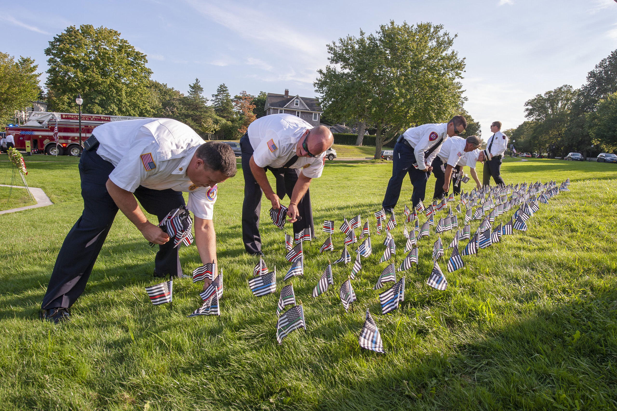 Firefighters from the Amagansett, Springs and Sag Harbor Fire Departments plant flags - one for each fire, police or military member killed at 9/11 - prior to the start of the ceremony commemorating the 20th anniversary of the attack on the World Trade Center, held on the Village Green in East Hampton on Saturday afternoon.