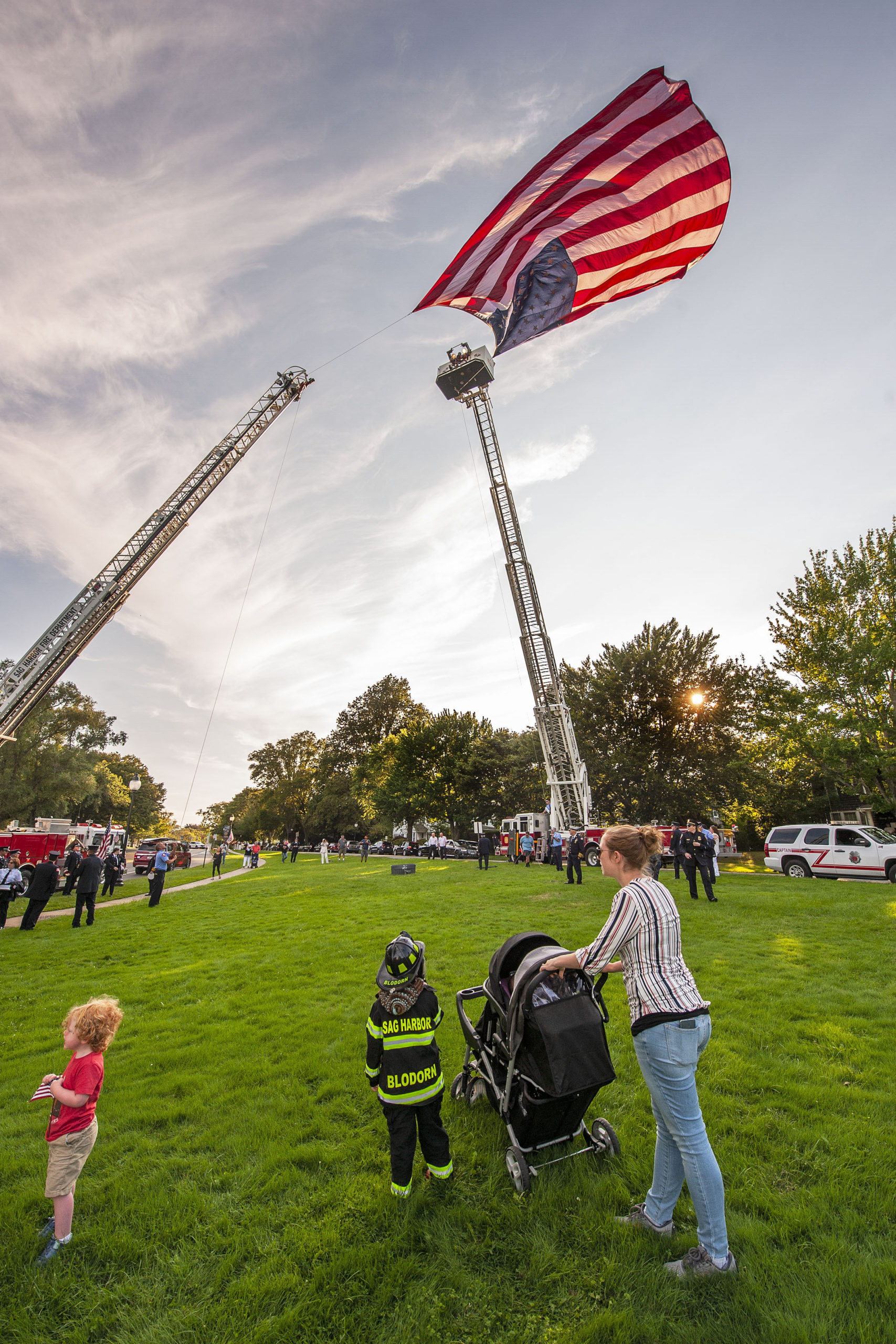 Five-year-old Connor Blodorn, son of Sag Harbor Fire Department Assistant Chief Andrew Blodorn, watches the American flag being raised by the East Hampton and Sag Harbor Fire Department ladder trucks prior to the start of the ceremony commemorating the 20th anniversary of the attack on the World Trade Center, held on the Village Green in East Hampton on Saturday afternoon.