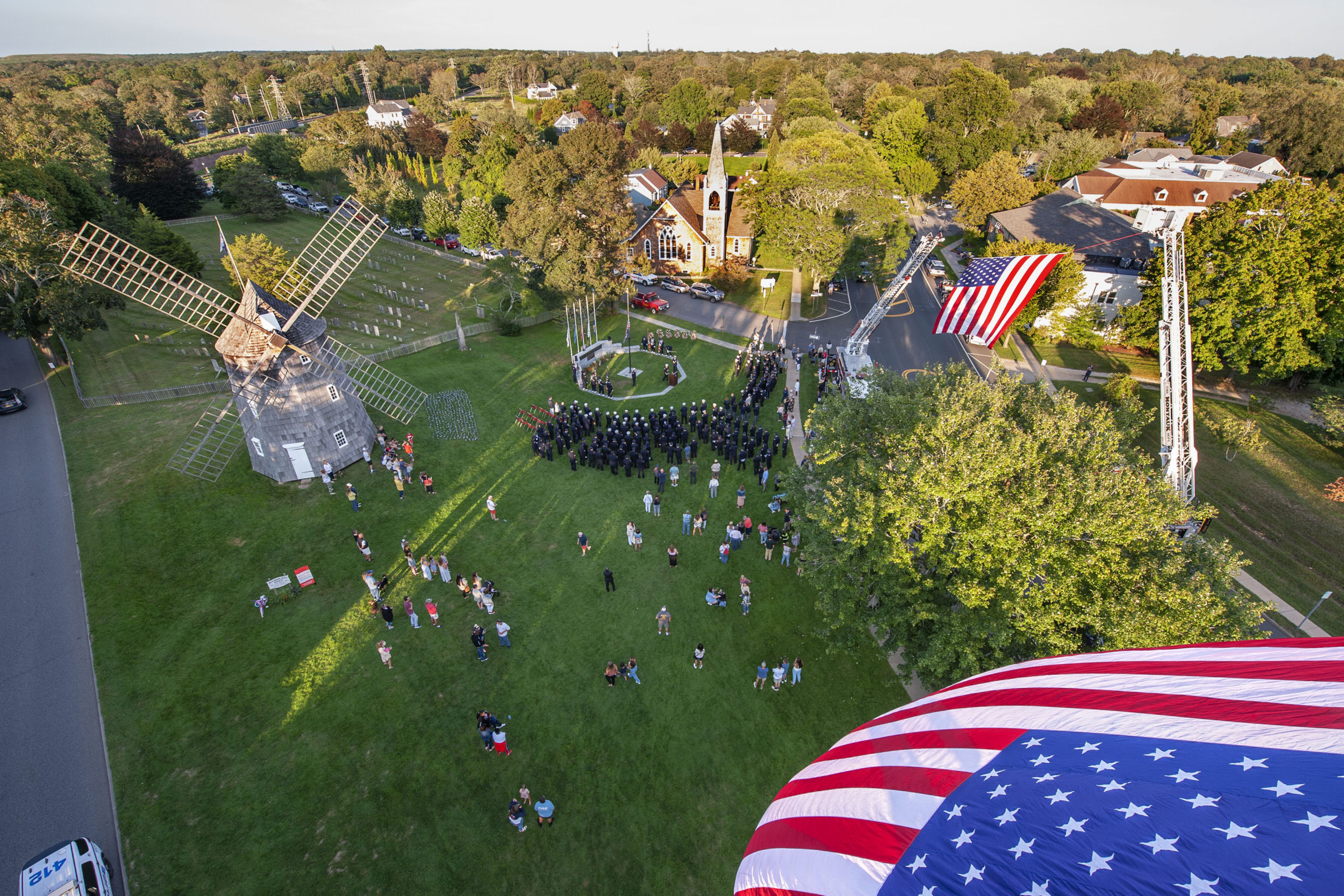 Large American flags fly over the East Hampton Village Green and Montauk Highway - courtesy of the East Hampton,  Sag Harbor, Bridgehampton and Montauk Fire Departments - during a ceremony commemorating the 20th anniversary of the attack on the World Trade Center, held on the Village Green in East Hampton and attended by 11 different East End fire, police and EMS agencies on Saturday afternoon.