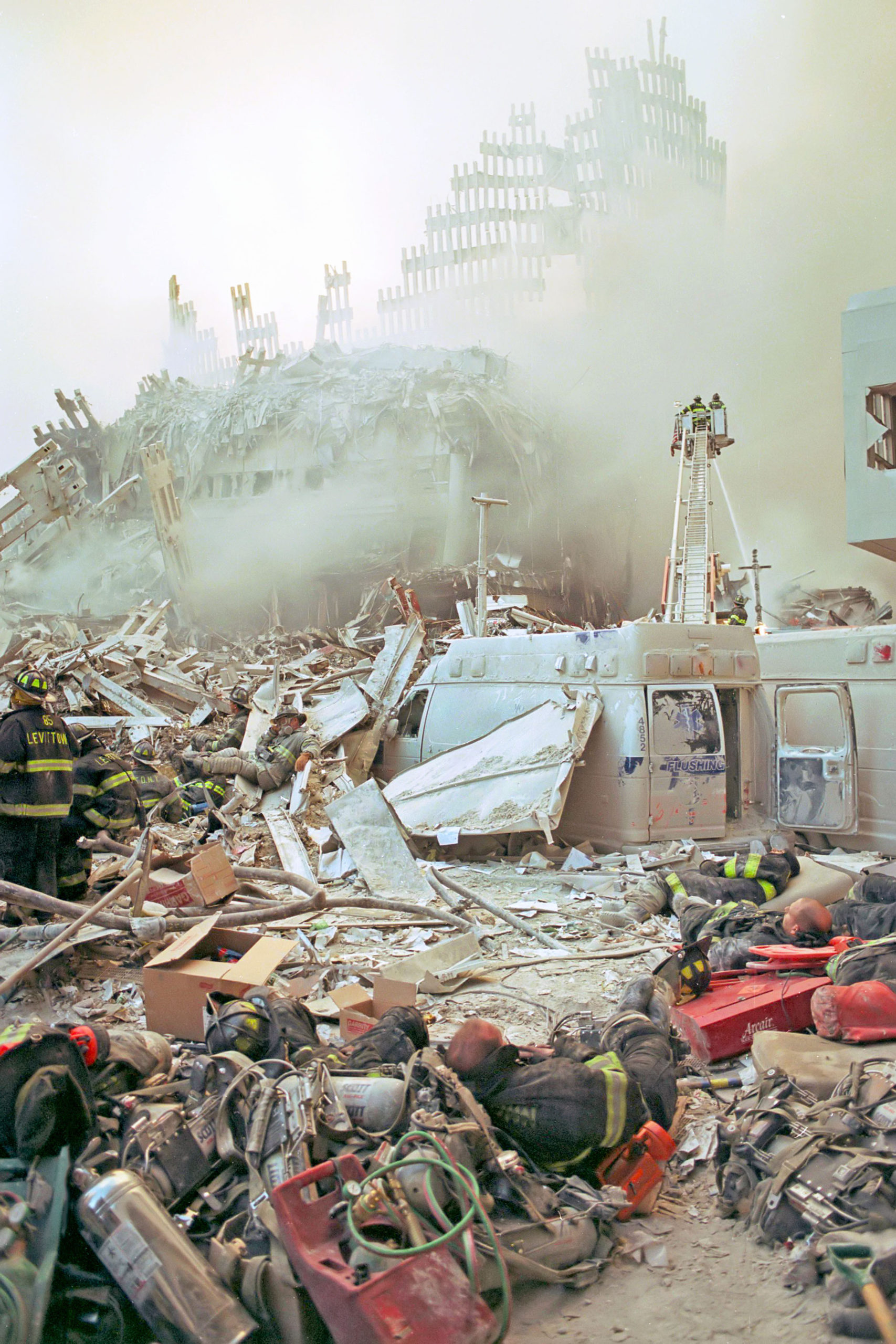 Exhausted firefighters sleep on the ground in the foreground; in the near background is the remains of the Marriot hotel, in front of the remains of the South Tower as seen from West Drive at about Liberty Street, looking east.     MICHAEL HELLER