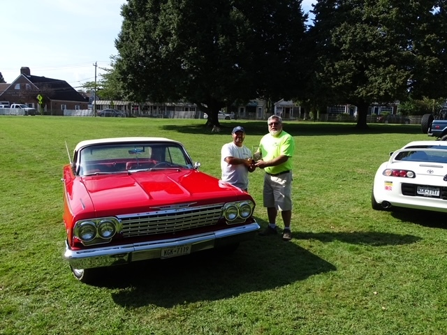 Todd Tureski presents the People's Choice trophy to Tom Federico, owner of the 1962 Chevy Impala SS, at the Water Mill Classic Car Show on Saturday.