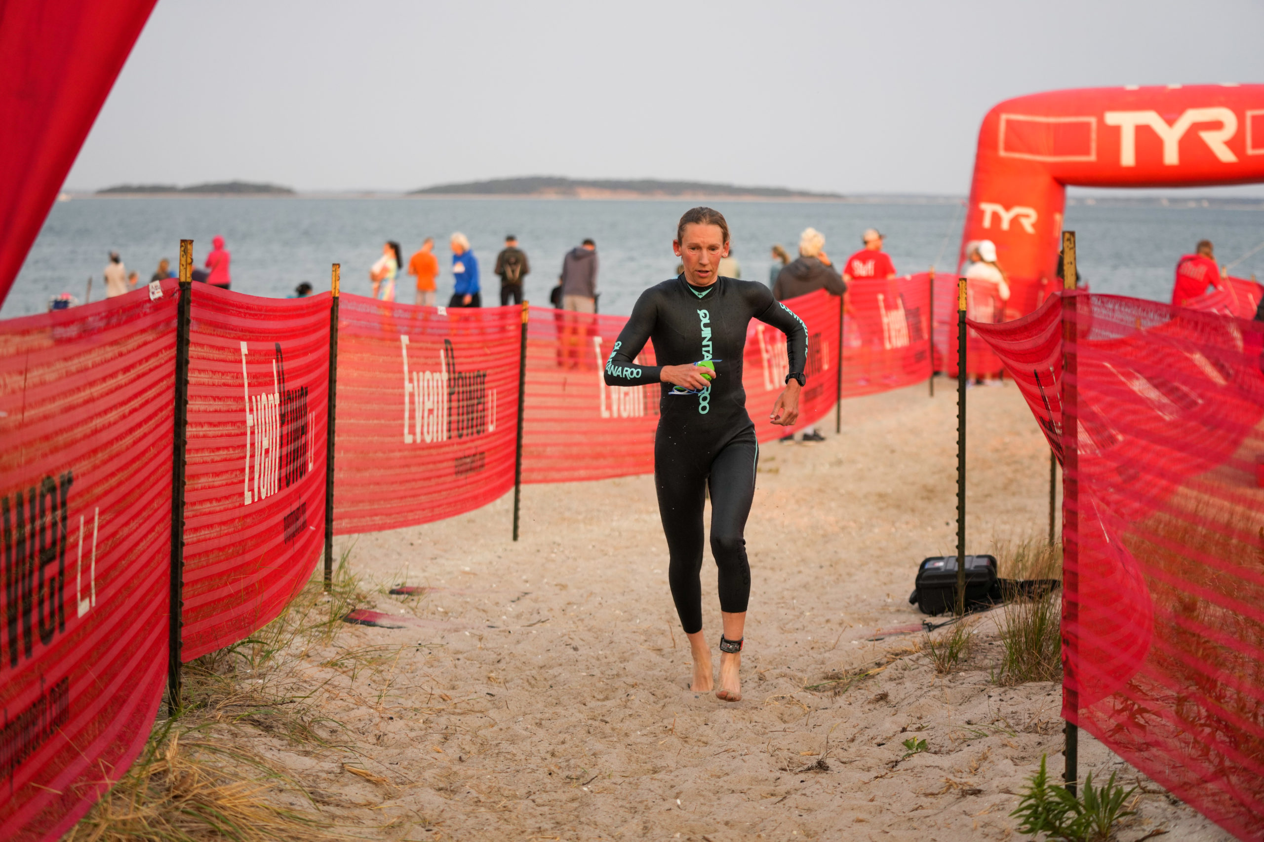 A triathlete transitions from the water to the bike area.