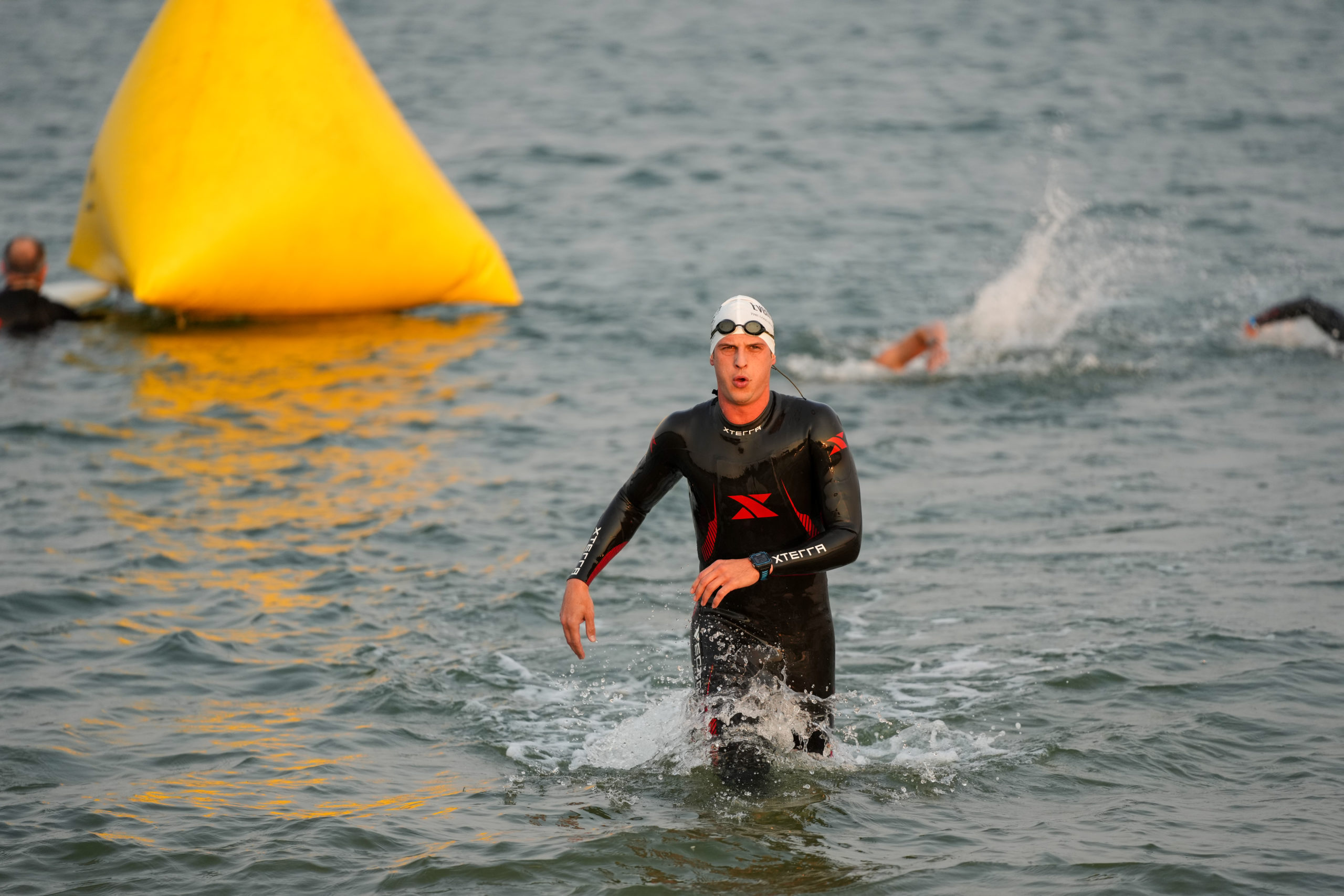 A triathlete gets out of the water.