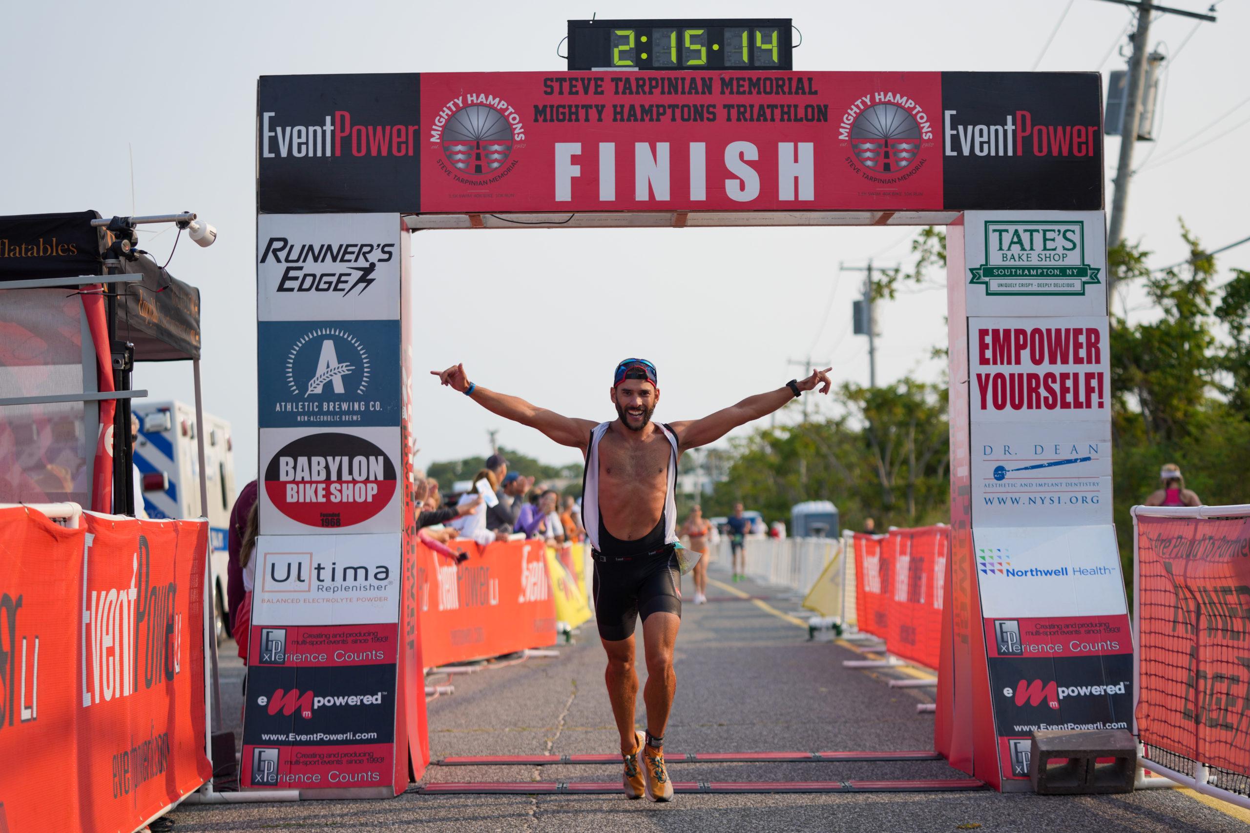 An athlete crosses the finish line of the Steve Tarpinian Memorial Mighty Hamptons Triathlon.