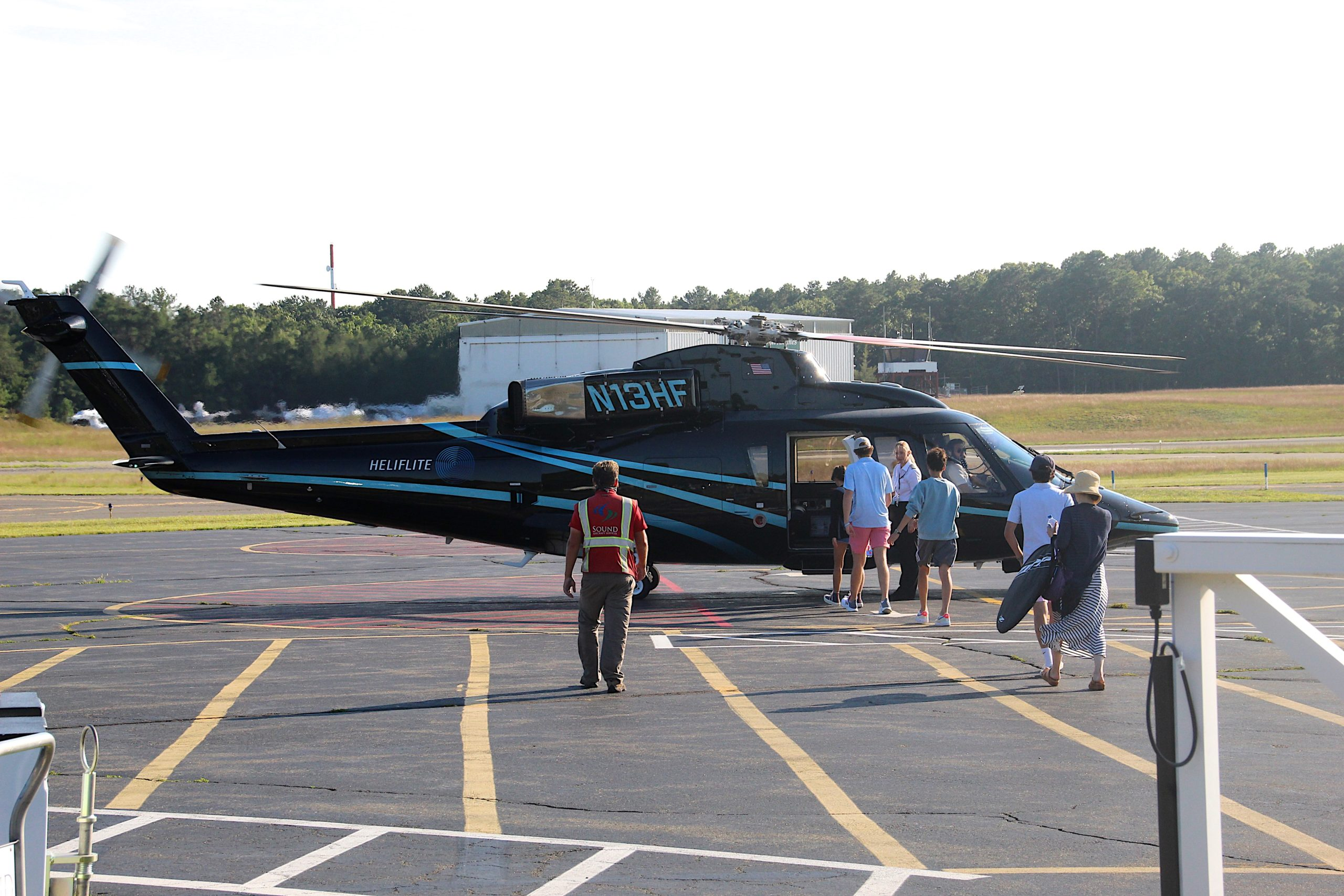 Passengers departing East Hampton Airport via helicopter on Monday afternoon. The town is analyzing how many helicopter and other plane flights would shift their flights to Montauk Airport if the East Hampton Airport were to close or place new limitations on the types of flights.