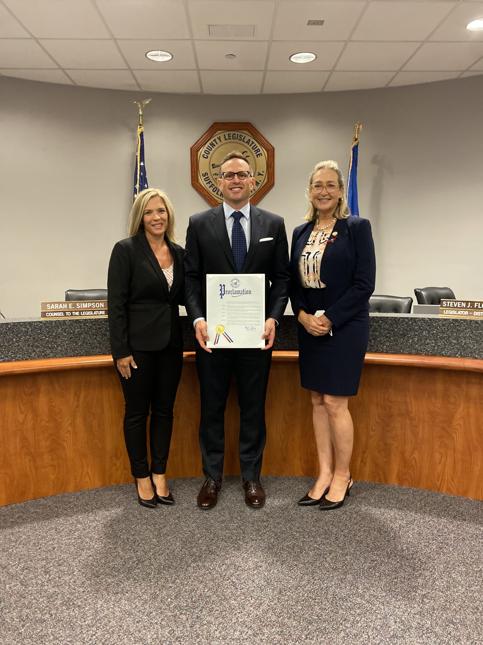 Suffolk County Legislator Bridget Fleming, right, presented Seth Korbin with a proclamation for his heroic action. At the presentation was Dr. Korbin's wife, Heidi, left.