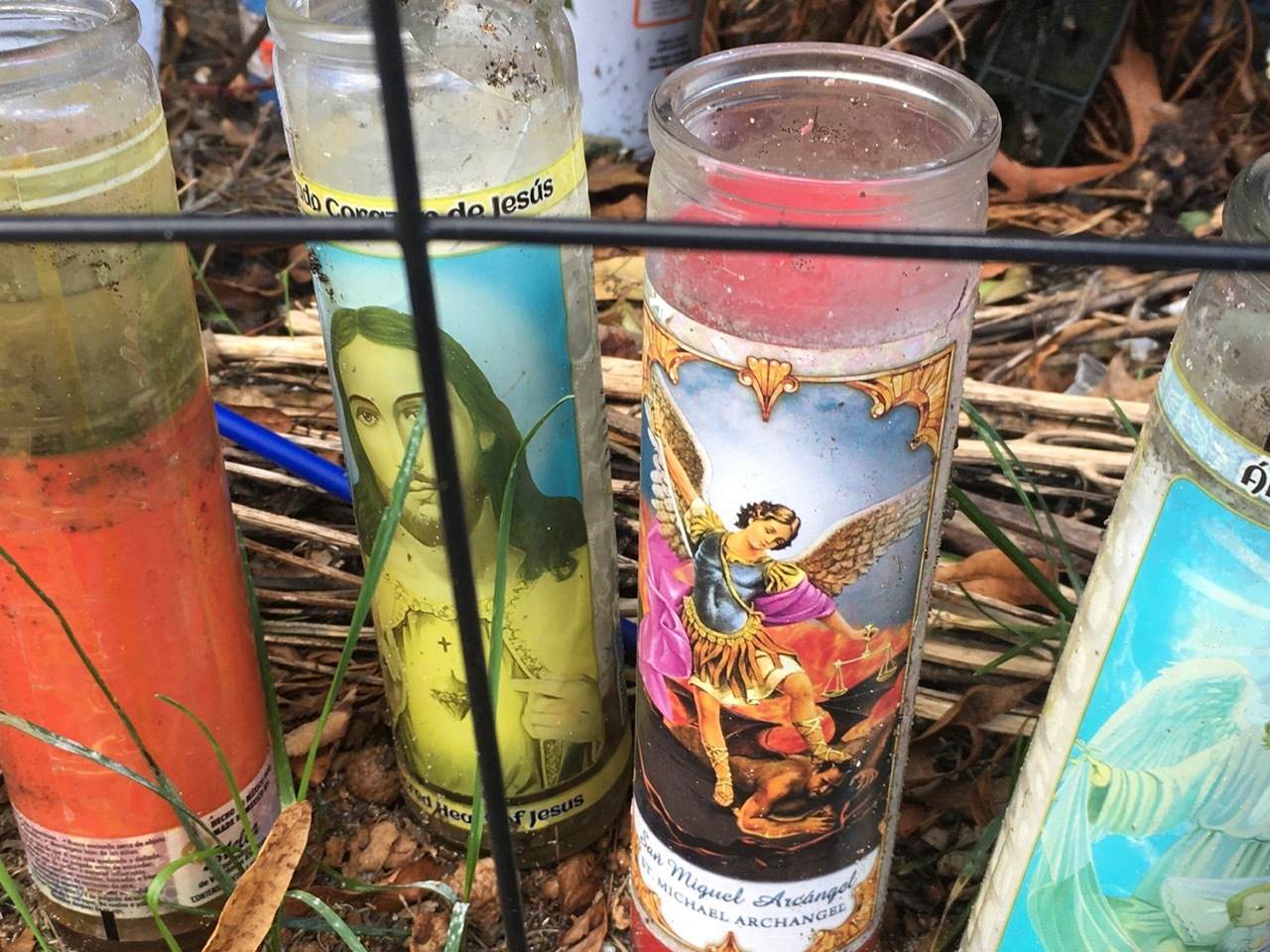 A cluster of religious candles is the focal point of a roadside memorial in Quogue.