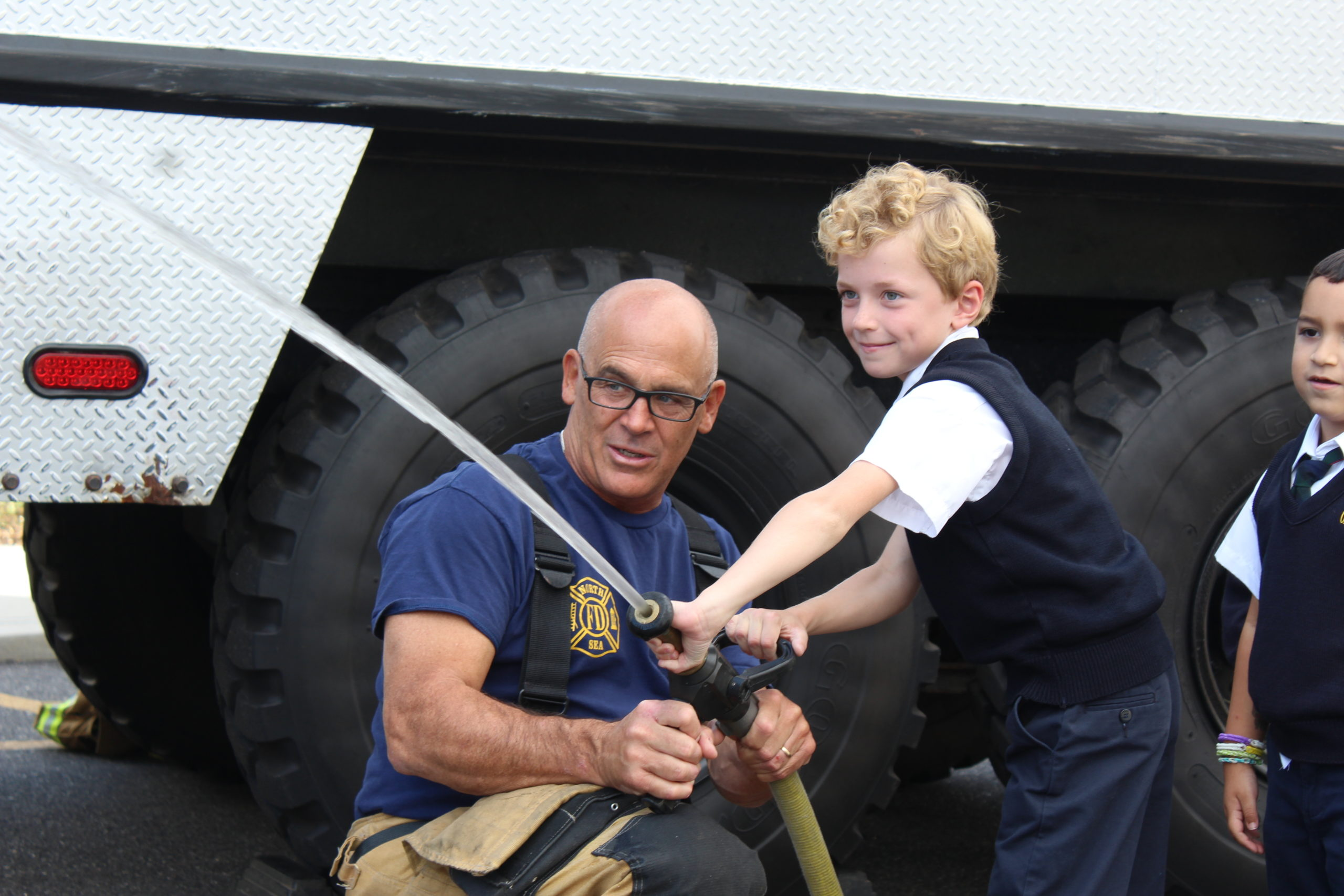Our Lady of the Hamptons School second-grader Oliver Fulweiler gets instruction on using the fire house from fireman Mark Hannan.