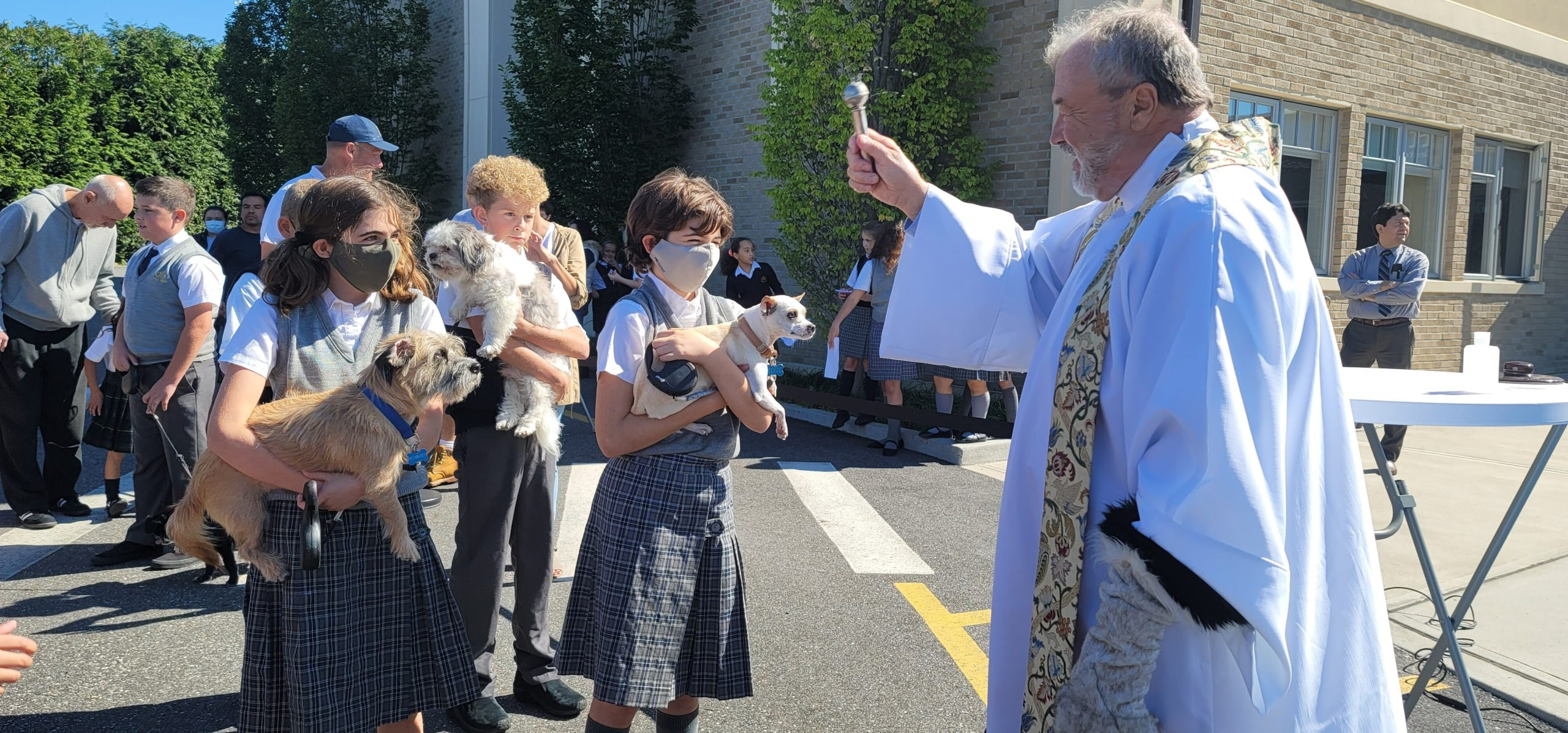 Our Lady of the Hamptons students Emma and LucyTillotson and Brian Spellman bring their pets to to be blessed during the annual Blessing of the Animals.