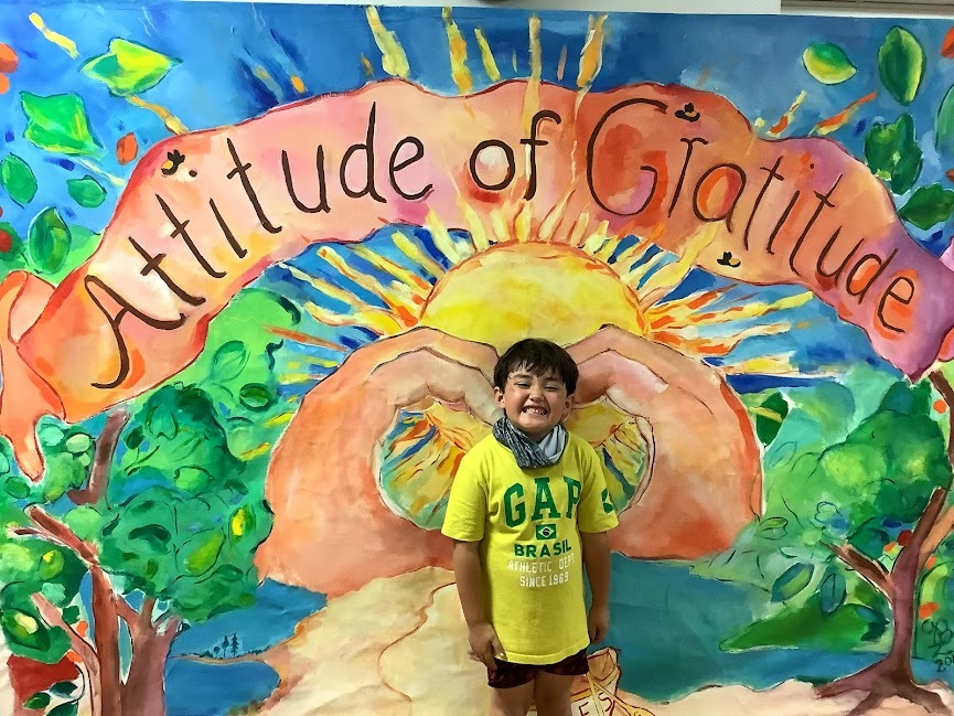 """One at a time, students posed in front of the mural designated to the school theme, """"Attitude of Gratitude."""""""